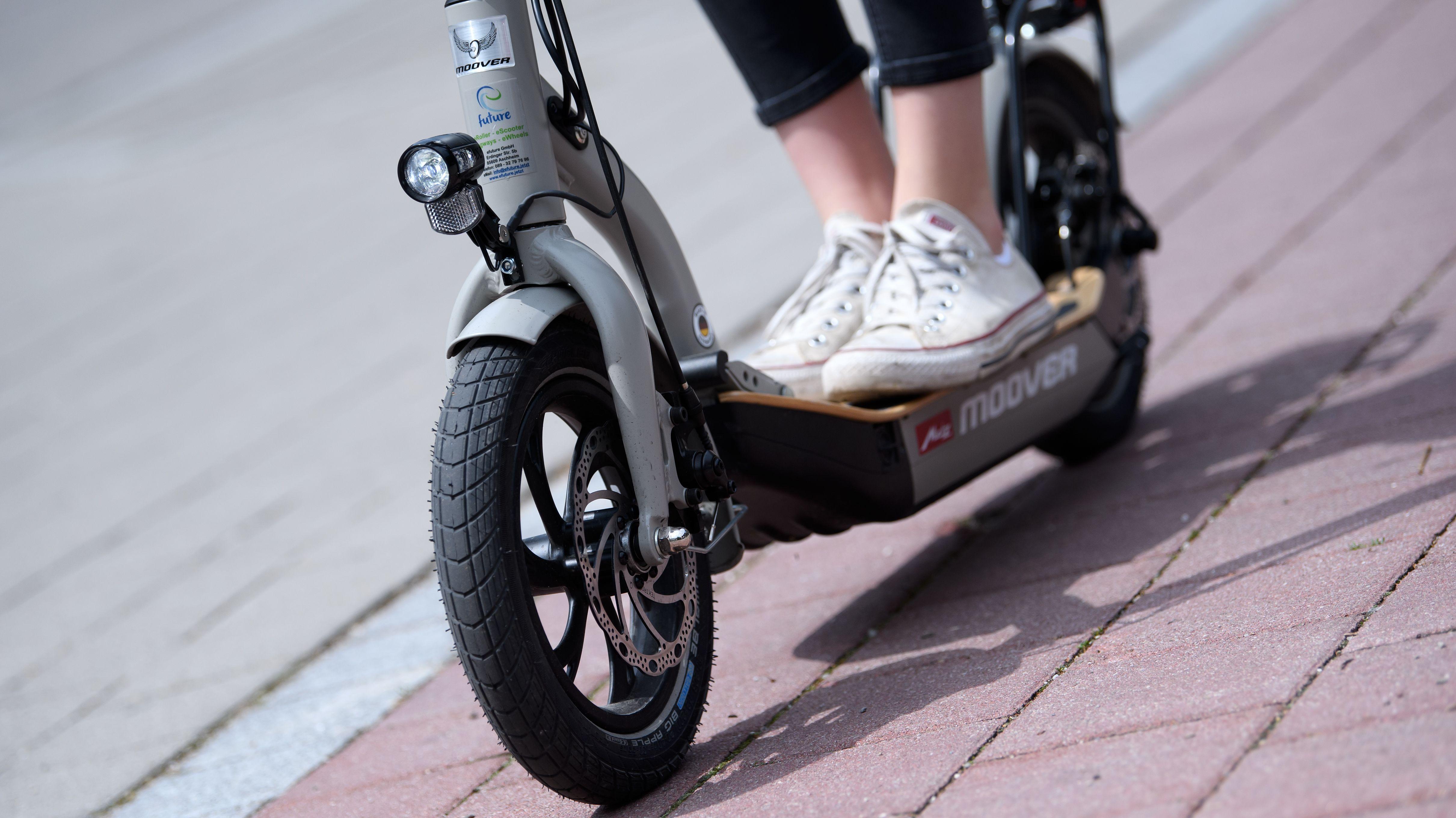 Füße in Turnschuhen auf einem E-Scooter