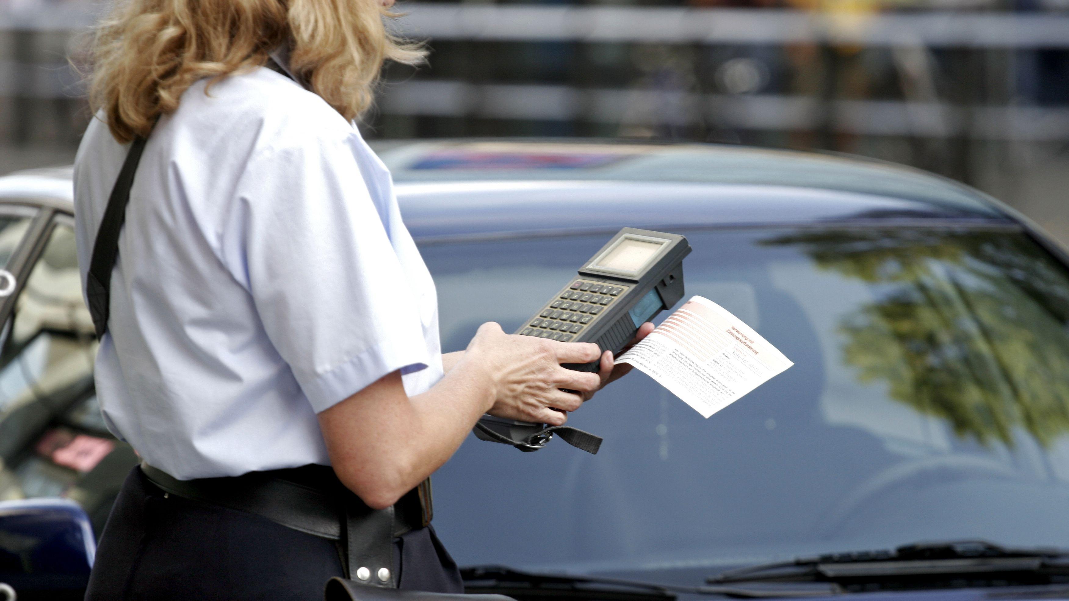 Eine Mitarbeiterin des Münchener Ordnungsamtes stellt einen Strafzettel aus
