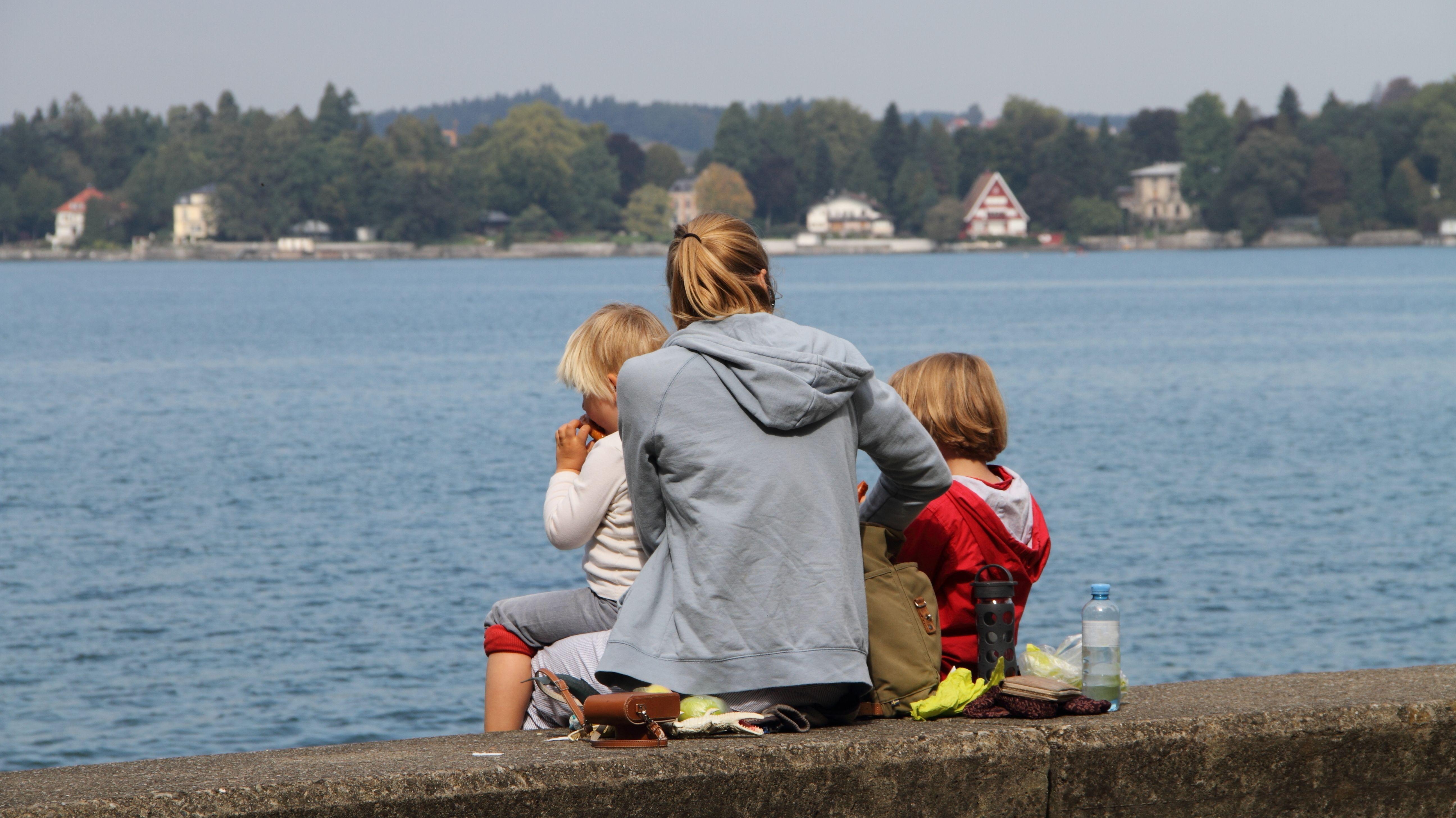 Eine Mutter sitzt mit ihren beiden Kindern am Ufer eines Sees.