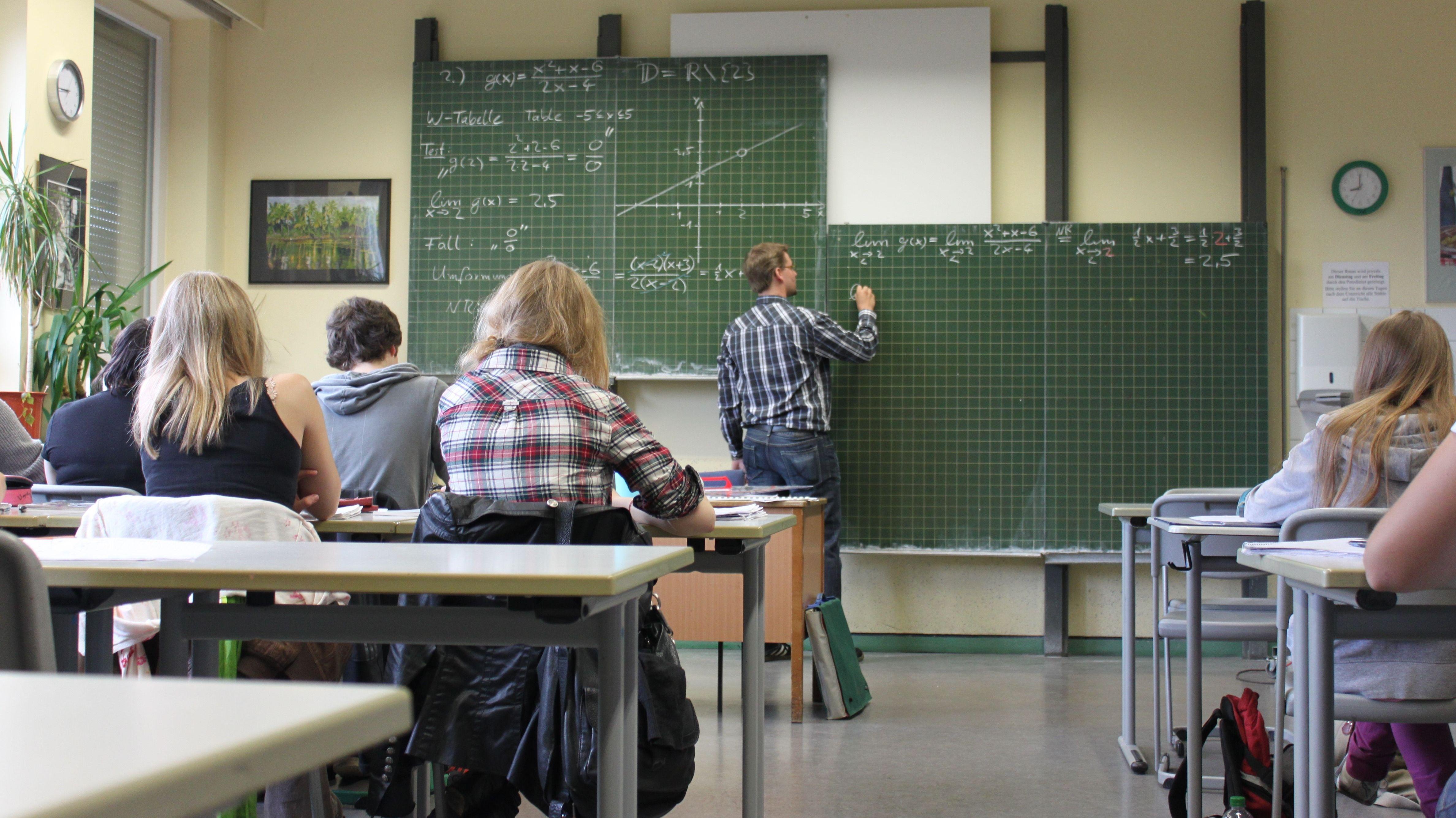 Das Bild zeigt Schülerinnen und Schüler im Teenageralter, die im Mathematikunterricht sitzen. Ein Lehrer schreibt Formeln an die Tafel.