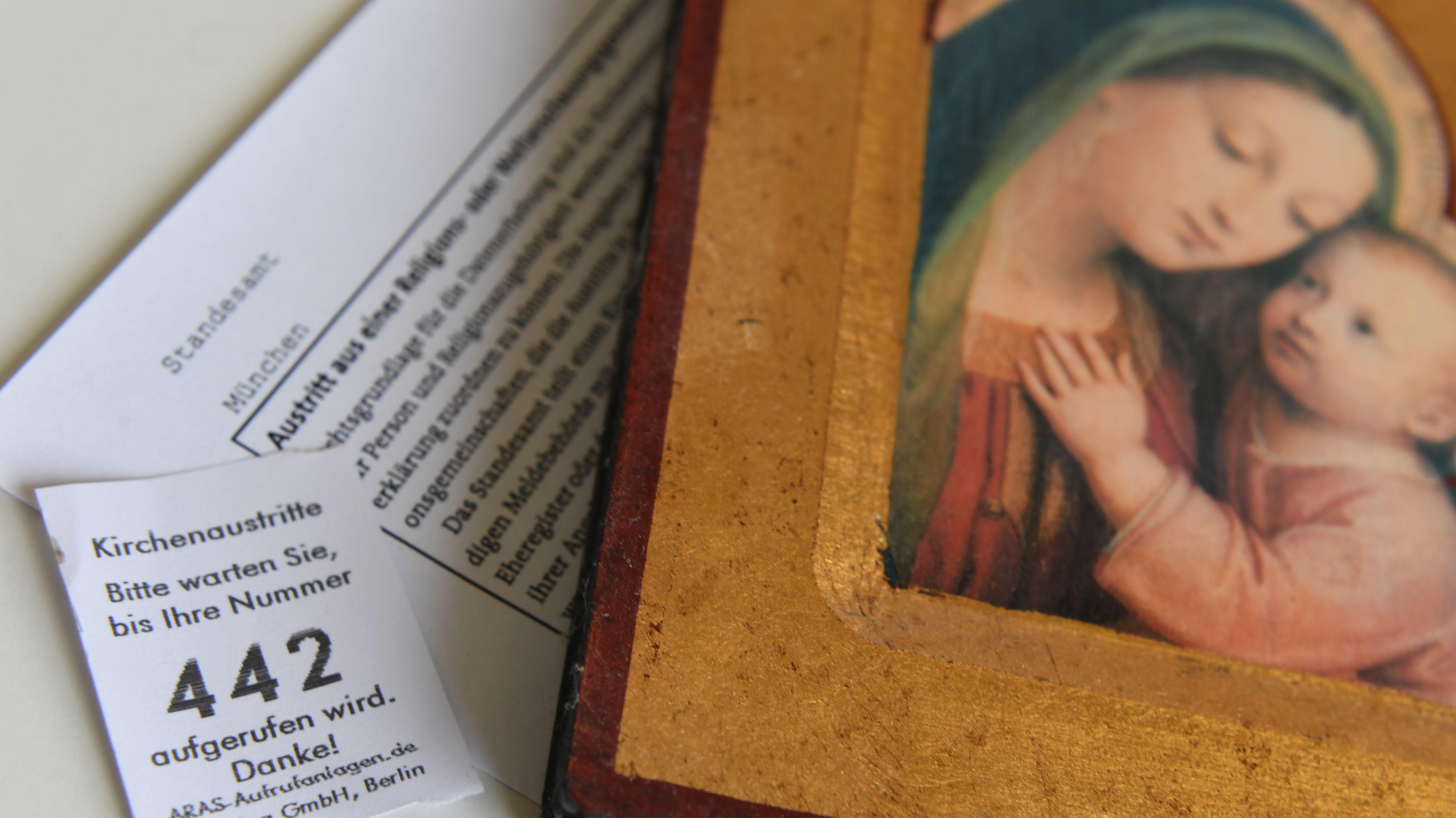 Eine Wartemarke, eine Urkunde zum Kirchenaustritt und eine christliche Ikone mit Maria und dem Jesuskind liegt in München auf einem Tisch.