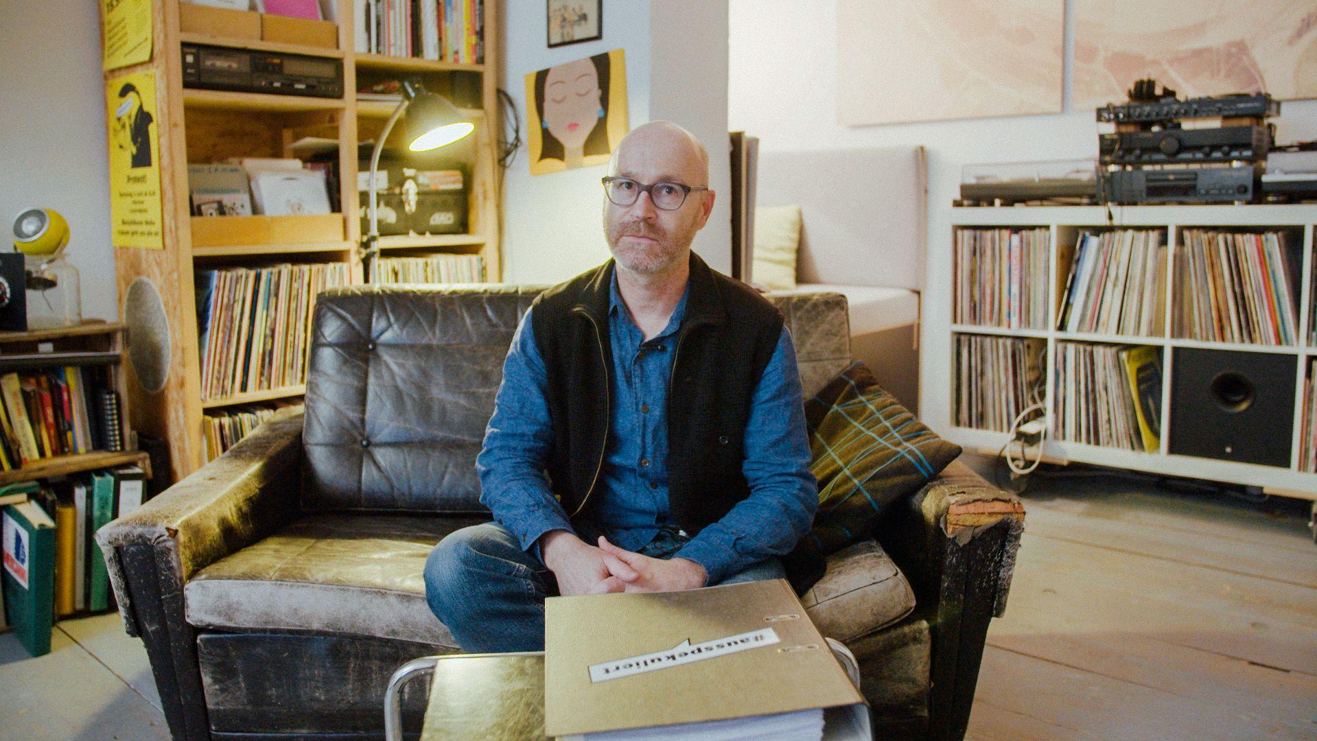 Ein Mieter sitzt in seiner Wohnung zwischen Schallplatten auf einem Sofa.