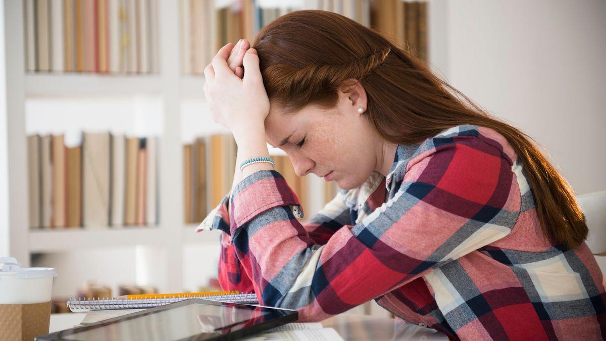 Verzweifelte Schülerin mit Tablet und Schreibblock