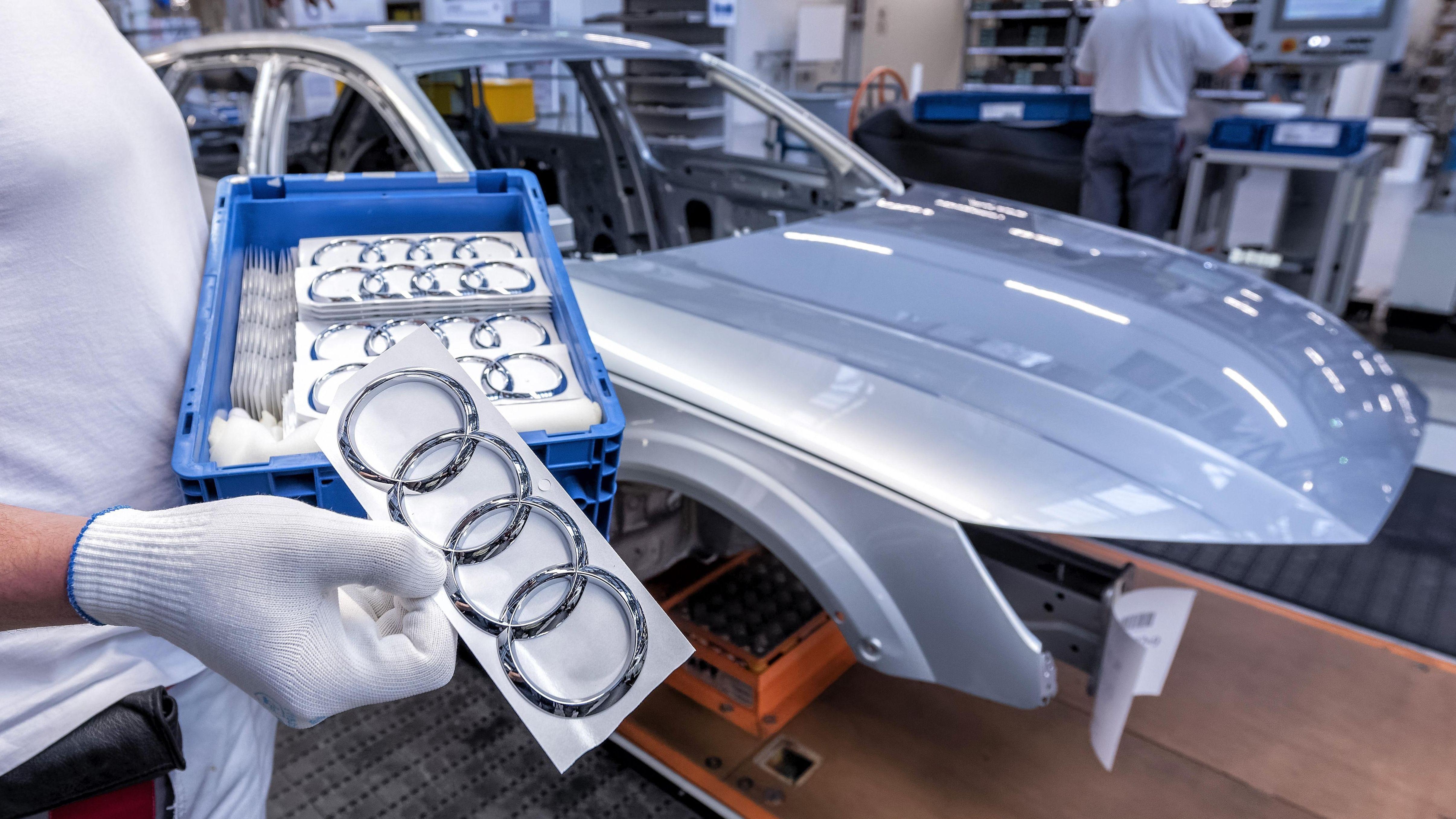 Ein Audi-Mitarbeiter hält einen Kasten mit Audi-Logos in Händen auf der Montagelinie Audi A4 im Werk der Audi AG in Ingolstadt.