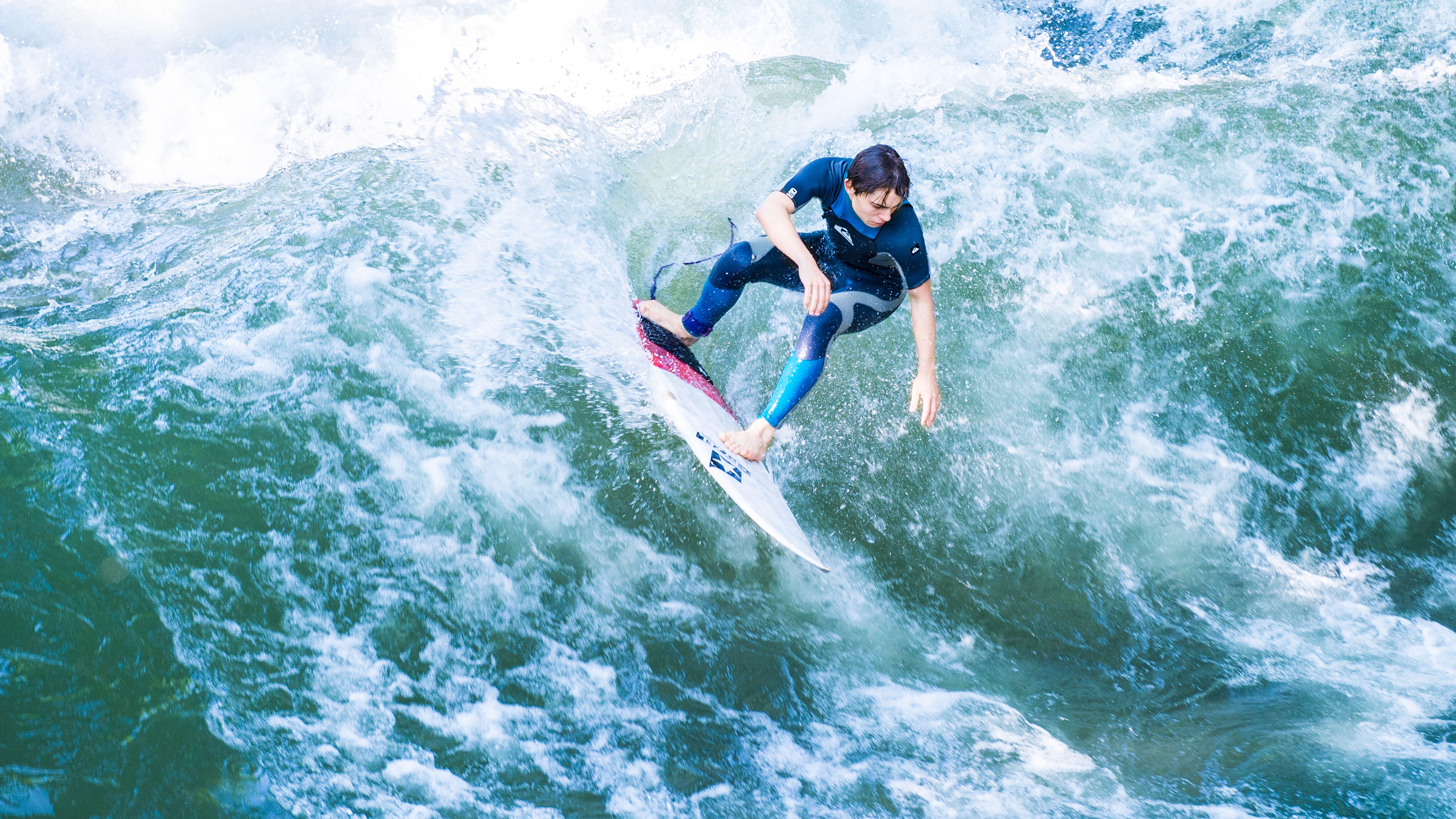 Surfer auf der Eisbachwelle in München. Auch in Wolfratshausen soll bald das Surfen auf einer künstlichen Welle möglich sein.
