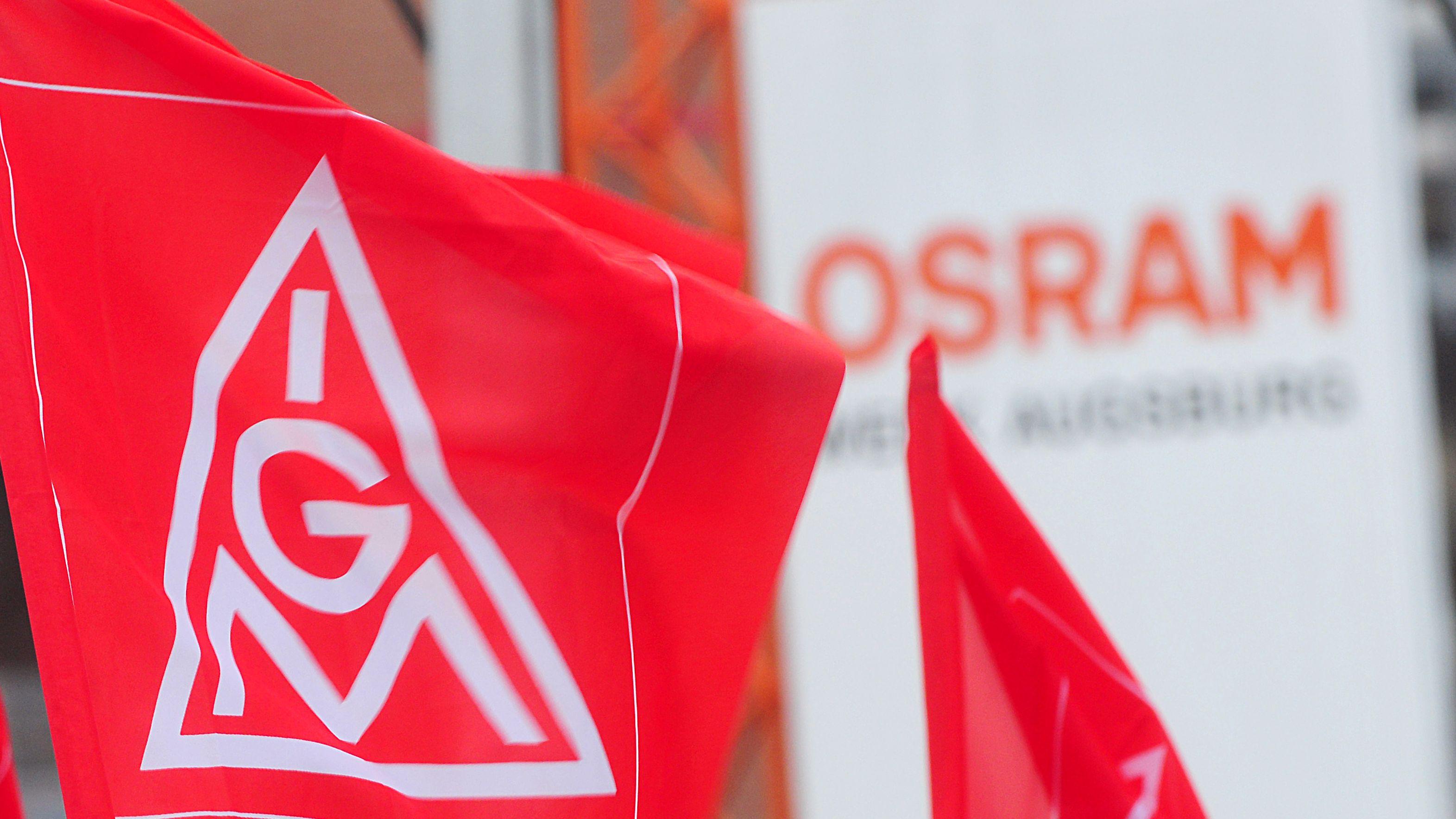 Eine IG-Metall-Fahne wird vor dem Firmenlogo von Osram gehalten.