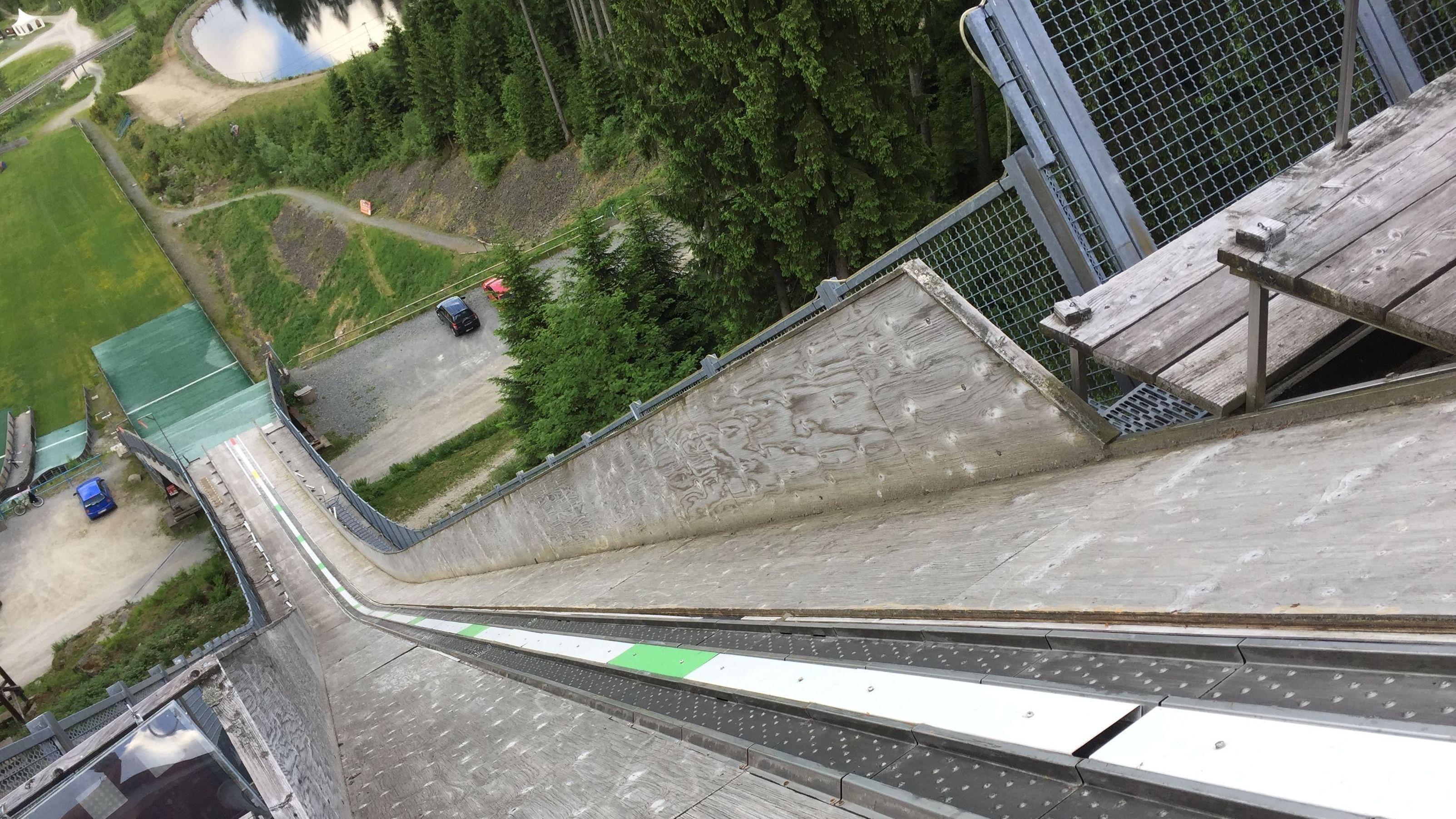 Die Sprungschanze in Bischofsgrün im Sommer von oben gesehen mit Bäumen im Hintergrund