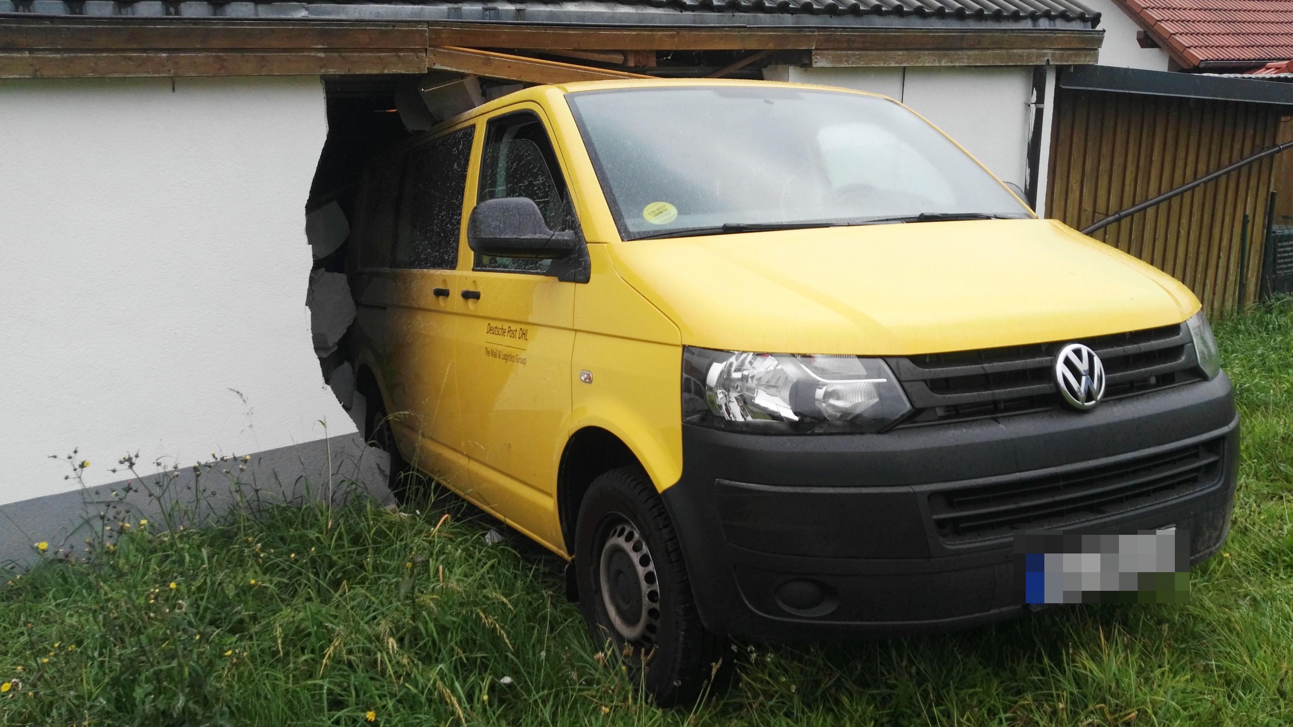 Postauto, das durch eine Garagenwand in Selb gebrochen ist