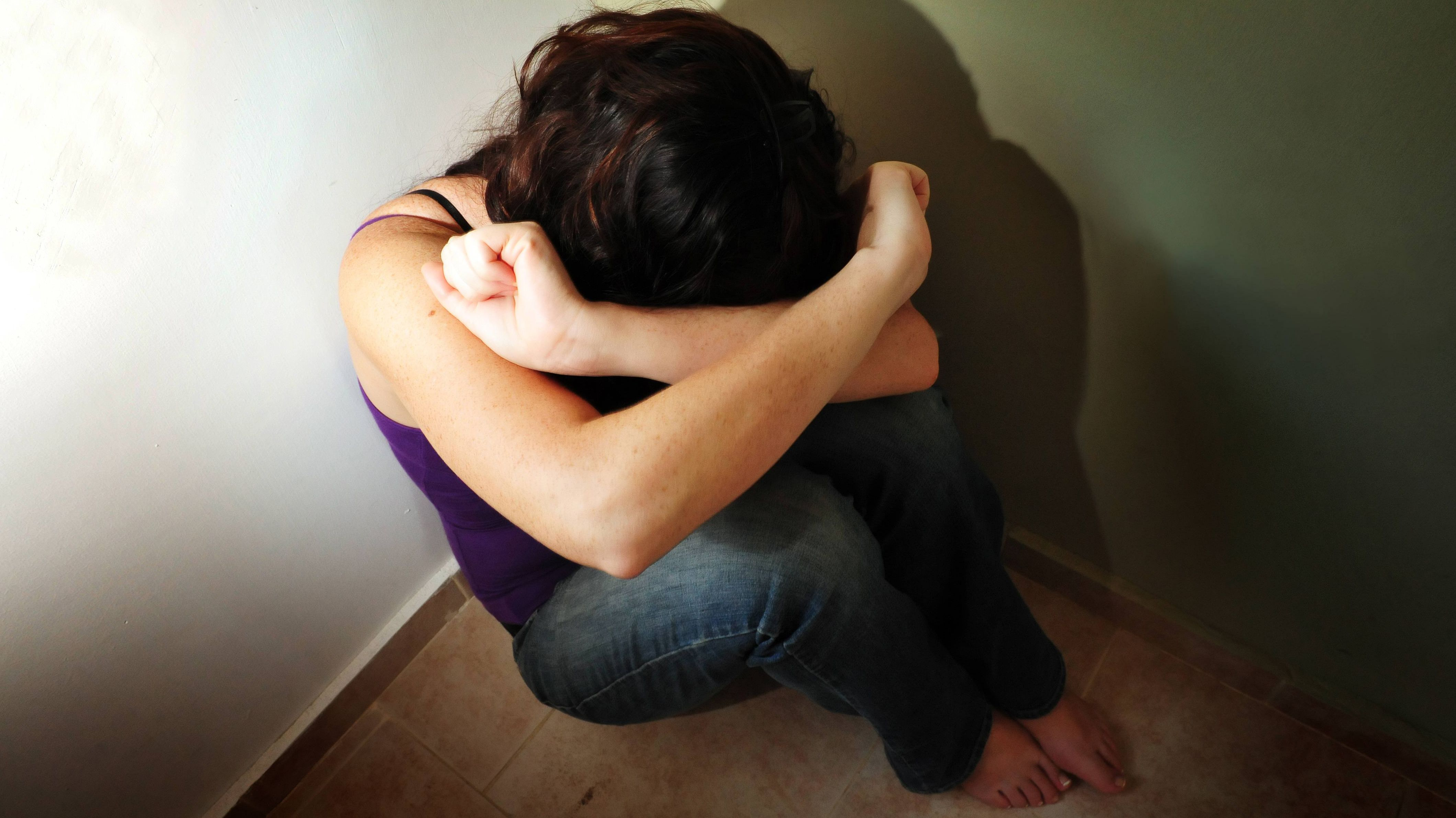 Mädchen sitzt verzweifelt in der Ecke und hält sich die Arme vors Gesicht
