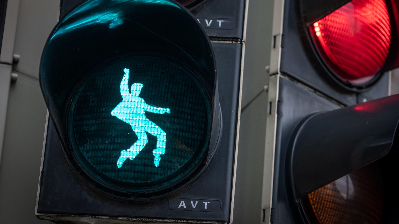 Ein Ampel-Männchen in Form eines tanzenden Elvis Presely leuchtet bei Grün an einer Fußgänger-Ampel am Elvis-Presley-Platz in Friedberg (Hessen) auf.
