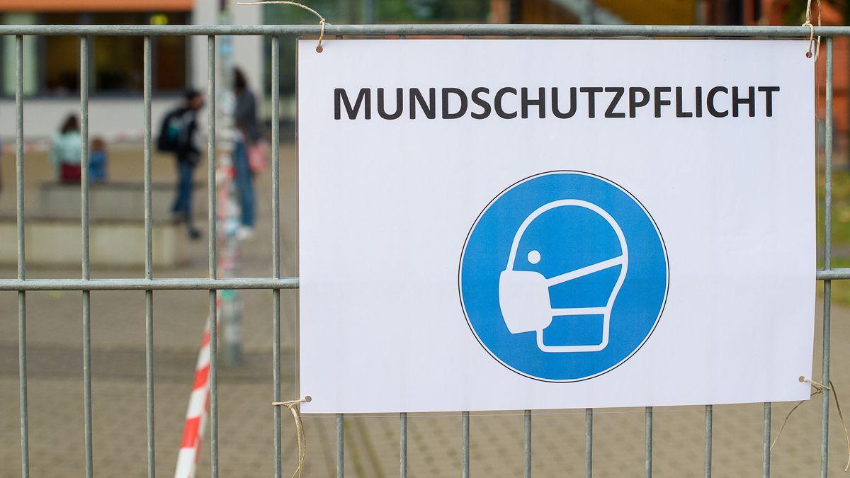 """""""Mundschutz"""" und ein Piktogramm eines maskentragenden Menschen sind auf einem Schild am Eingang einer Schule (Symbolbild)"""