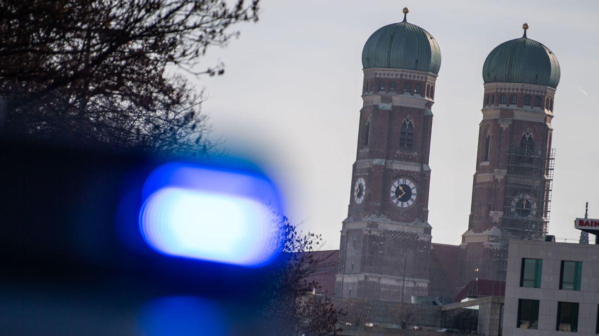 Ein Blaulicht einer Polizeistreife ist vor den Türmen der Frauenkirche zu sehen.