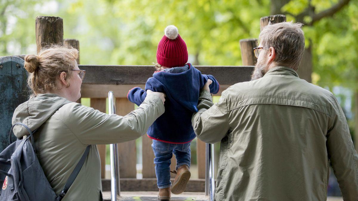 Vater, Mutter, Kind auf einem Spielplatz
