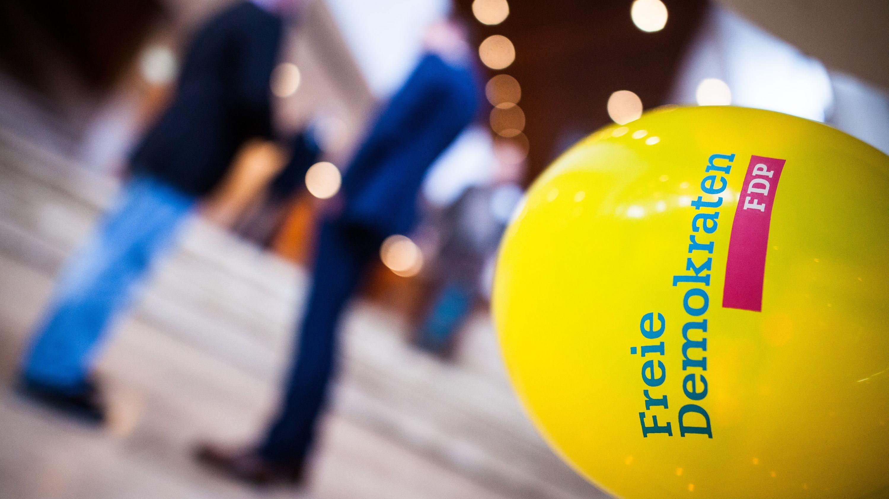 """Ein Luftballon mit der Aufschrift """"Freie Demokraten FDP"""" ist im Vordergrund zu sehen, dahinter verschwommen zwei Menschen (Symbolbild)"""
