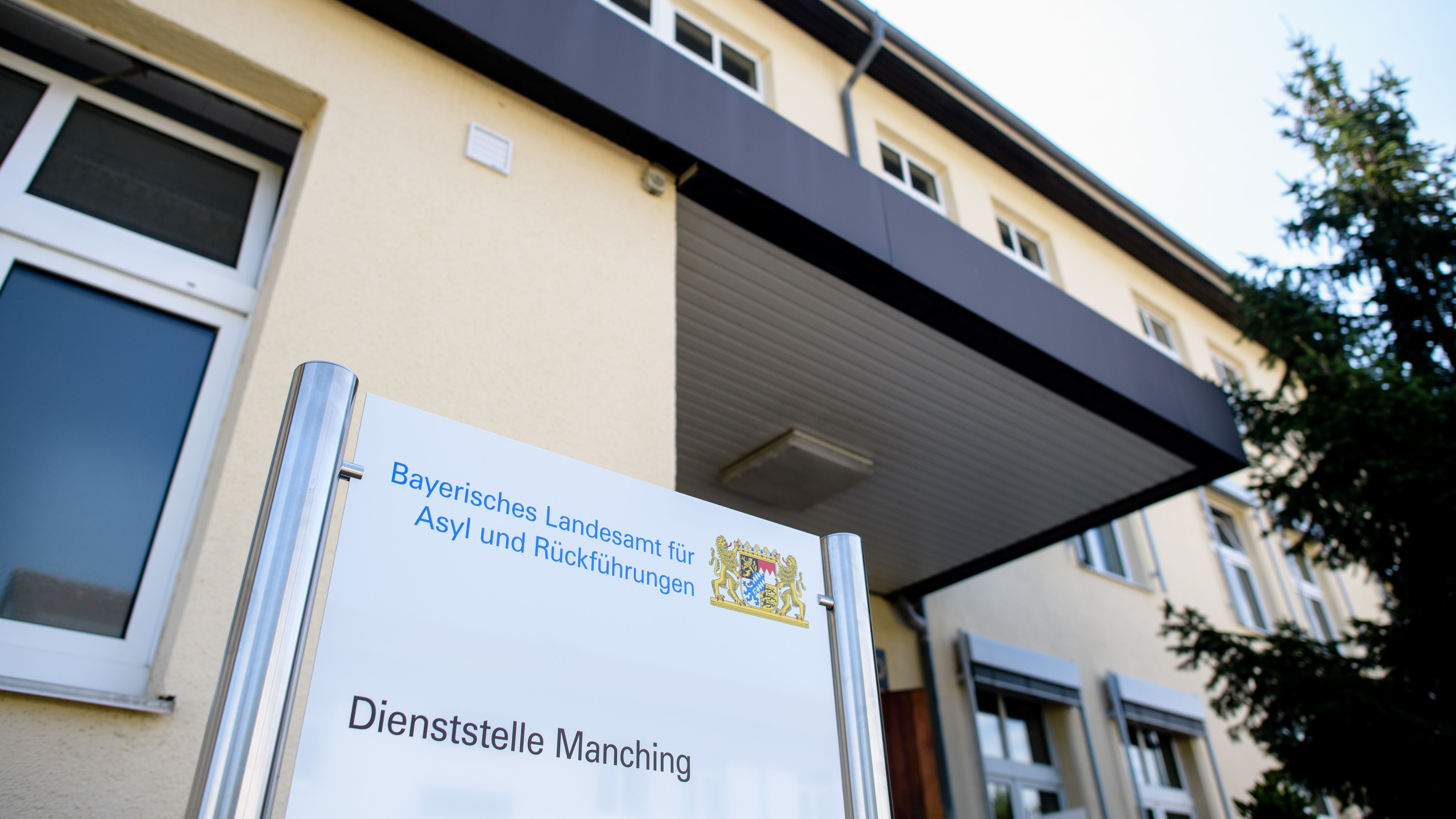 """Schild mit der Aufschrift """"Bayerisches Landesamt für Asyl und Rückführungen - Dienststelle Manching"""""""