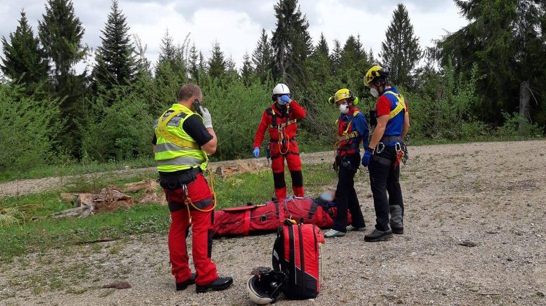 Die ehrenamtlichen Bergretter und die Hubschrauberbesatzung warten mit dem Patienten im Bergesack auf den Hubschrauber.
