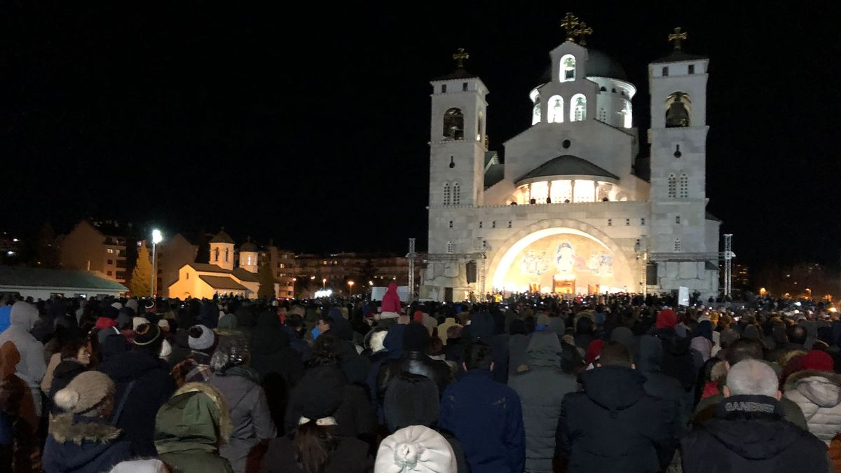 Menschenmenge vor einer Kirche bei Nacht.