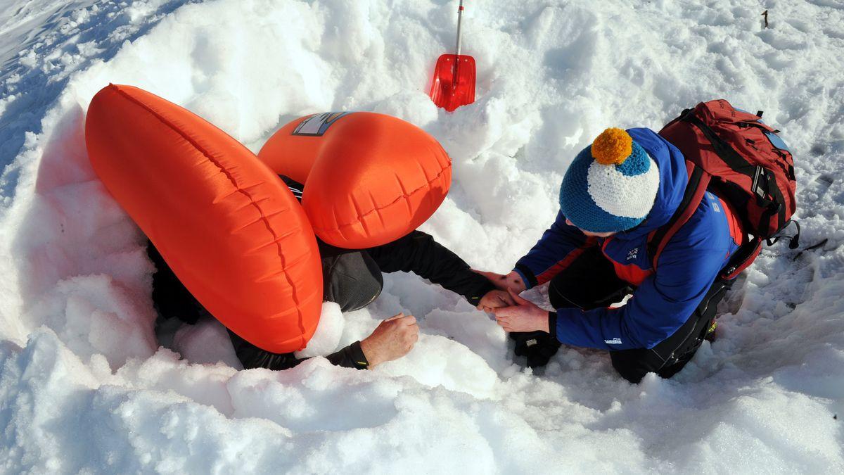 Mann mit Lawinenruckssack im Schnee mit Helfer.