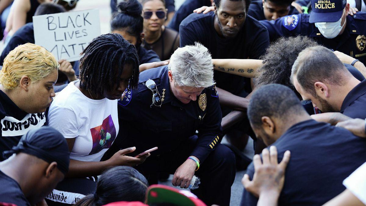 USA, Aurora: Demonstranten und Polizisten, darunter Chief Vanessa Wilson, knien gegen Polizeibrutalität und Rassismus.