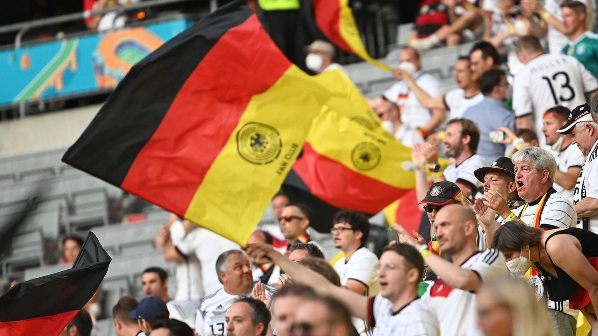 Fans feiern auf der Tribüne mit deutsche Fahnen vor dem Spiel.