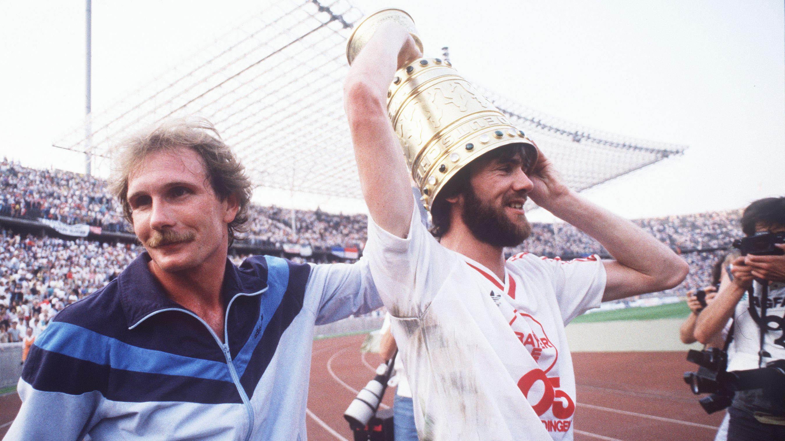 Friedhelm Funkel trägt den DFB-Pokal 1985 auf dem Kopf und feiert mit Wolfgang Schäfer.