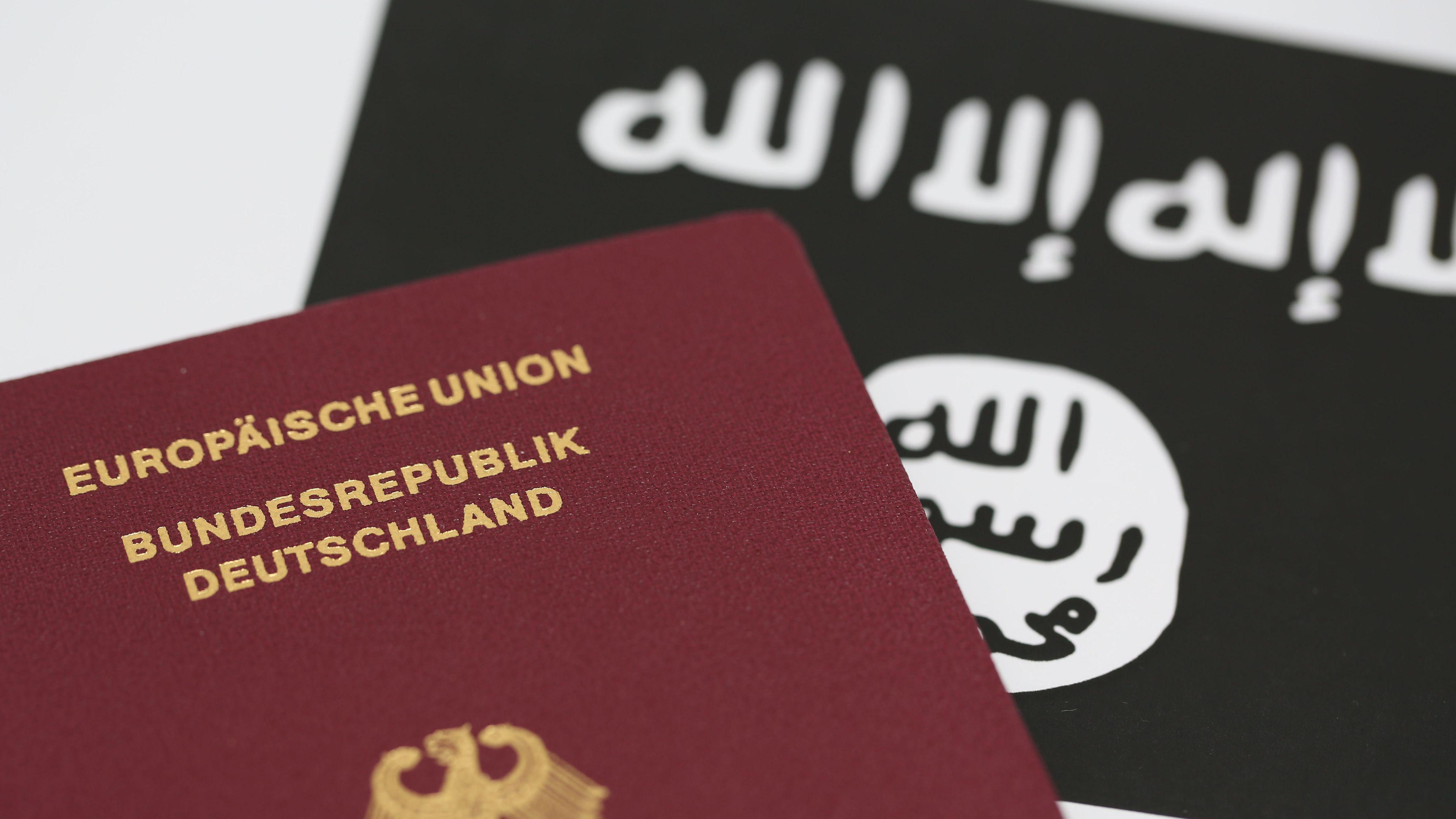 Reisepass der Bundesrepublik Deutschland vor der Flagge des so genannten Islamischen Staates (IS).