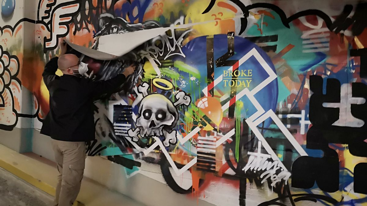 Künstler nimmt eine Stoffleinwand von der bemalten Wand.