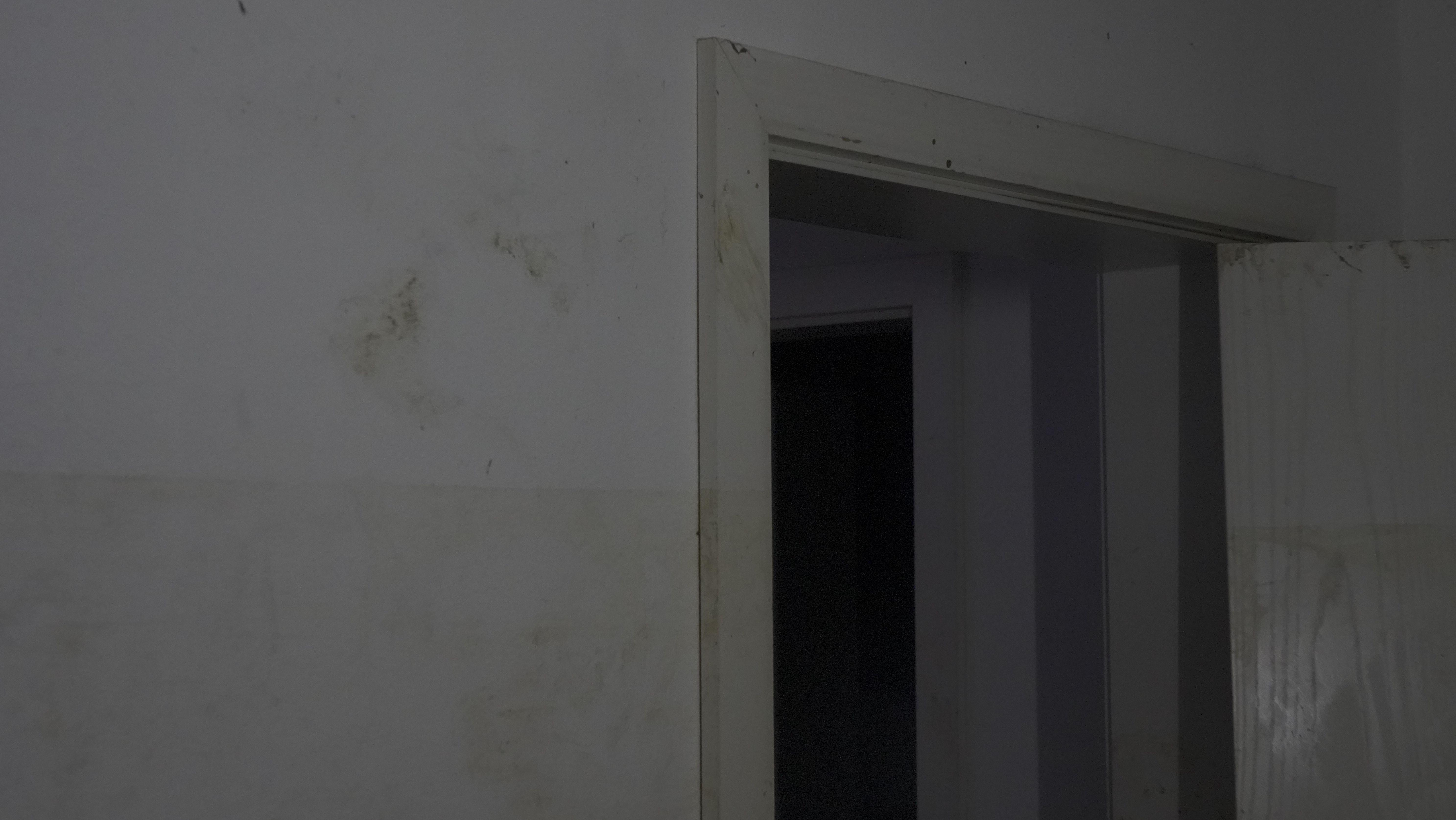Braune Linie an einem weißen Türrahmen.
