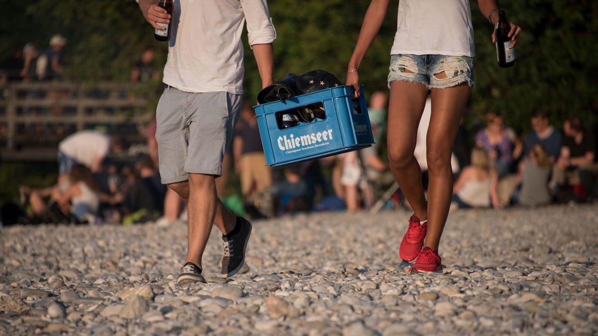 Junge Leute tragen am Flaucher an der Isar einen Kasten Bier.