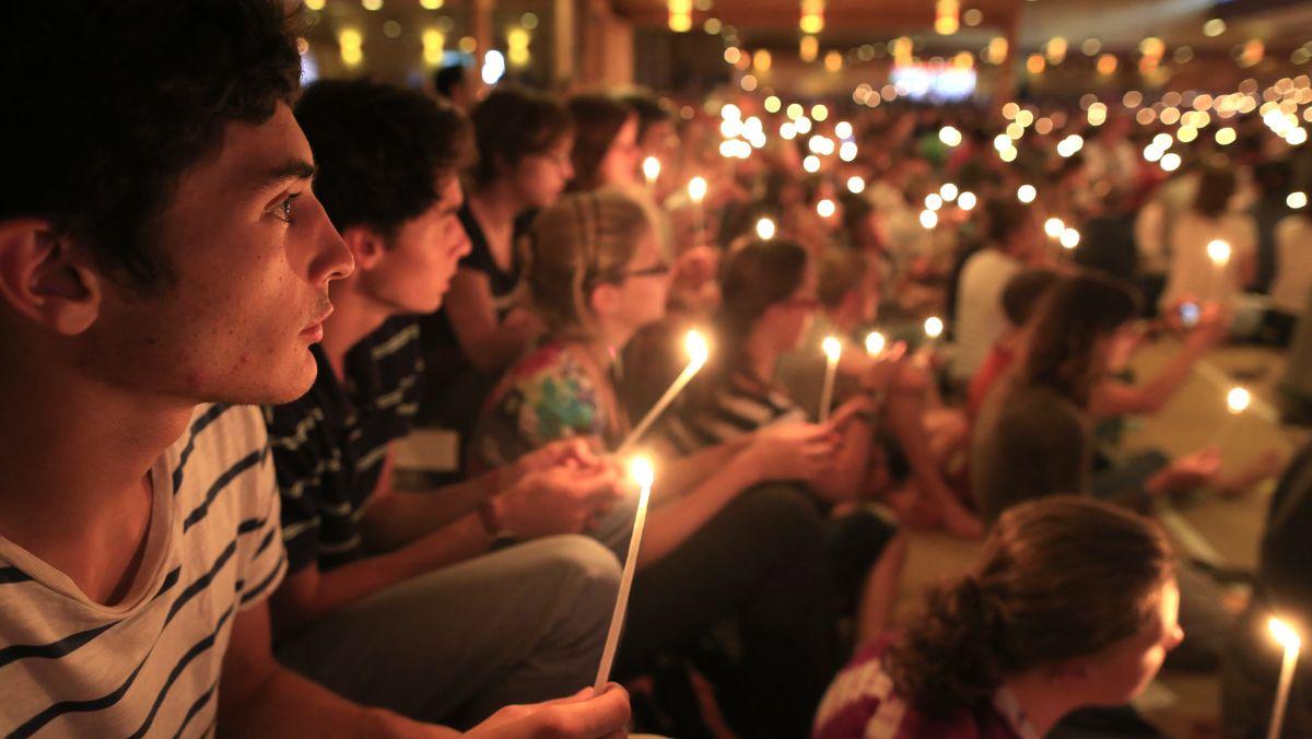 Jugendliche in Taizè  (hunderte Jugendliche sitzen mit Kerzen am Boden)