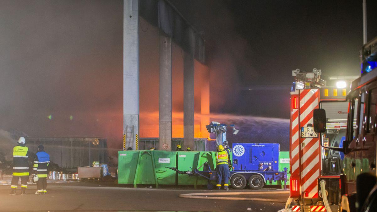 Die Feuerwehr löscht die brennenden Müllhaufen in die Lagerhalle