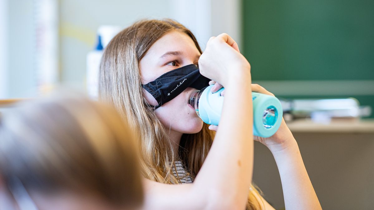 Eine Schülerin hebt ihren Mund-Nase-Schutz hoch und trinkt aus einer Flasche