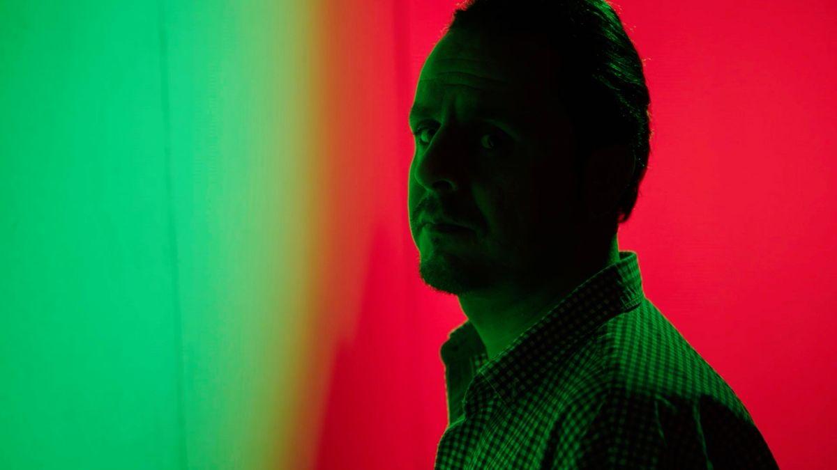 Der Musiker Pouya Raufyan steht vor einem farbigen Hintergrund, vom satten Rot geht es ins Grün über.