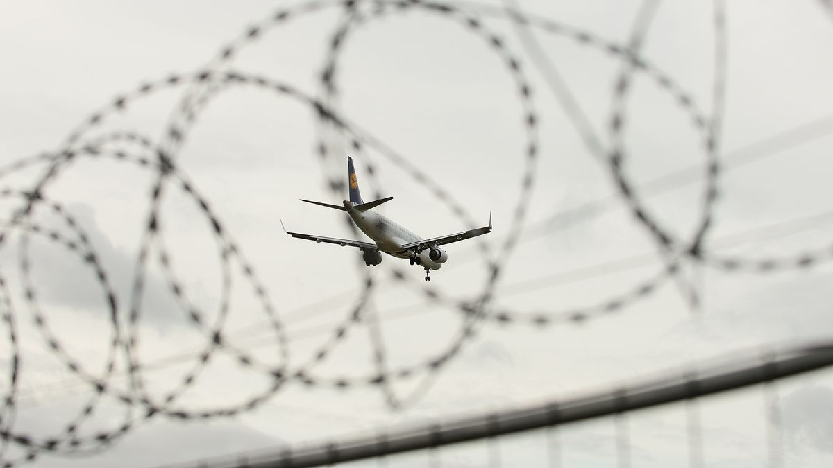 """Symbolbild """"Abschiebung"""": Eine Maschine der Lufthansa hinter Stacheldraht"""