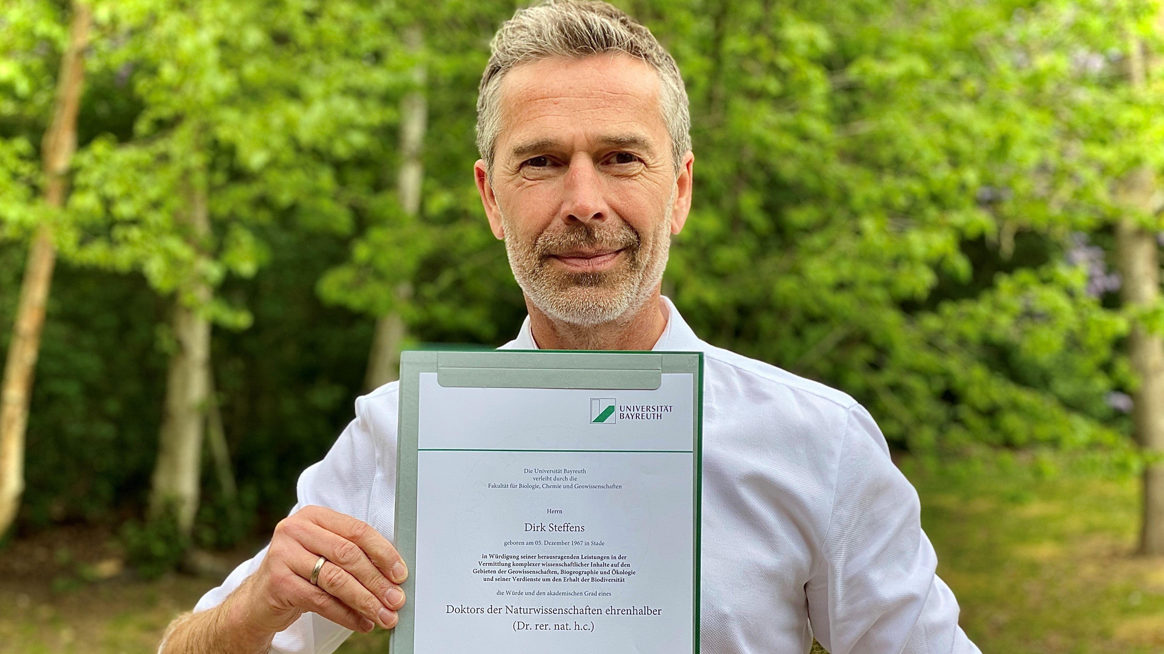 TV-Moderator und Wissenschaftskommunikator Dirk Steffens mit der Urkunde, die die Ehrendoktorwürde der Universität Bayreuth dokumentiert.