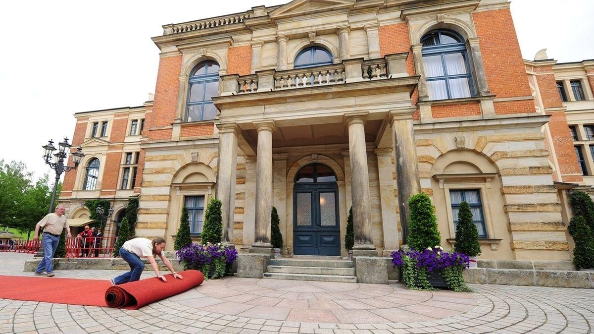 Vor dem Bayreuther Festspielhaus rollen Mitarbeiter einen roten Teppich aus