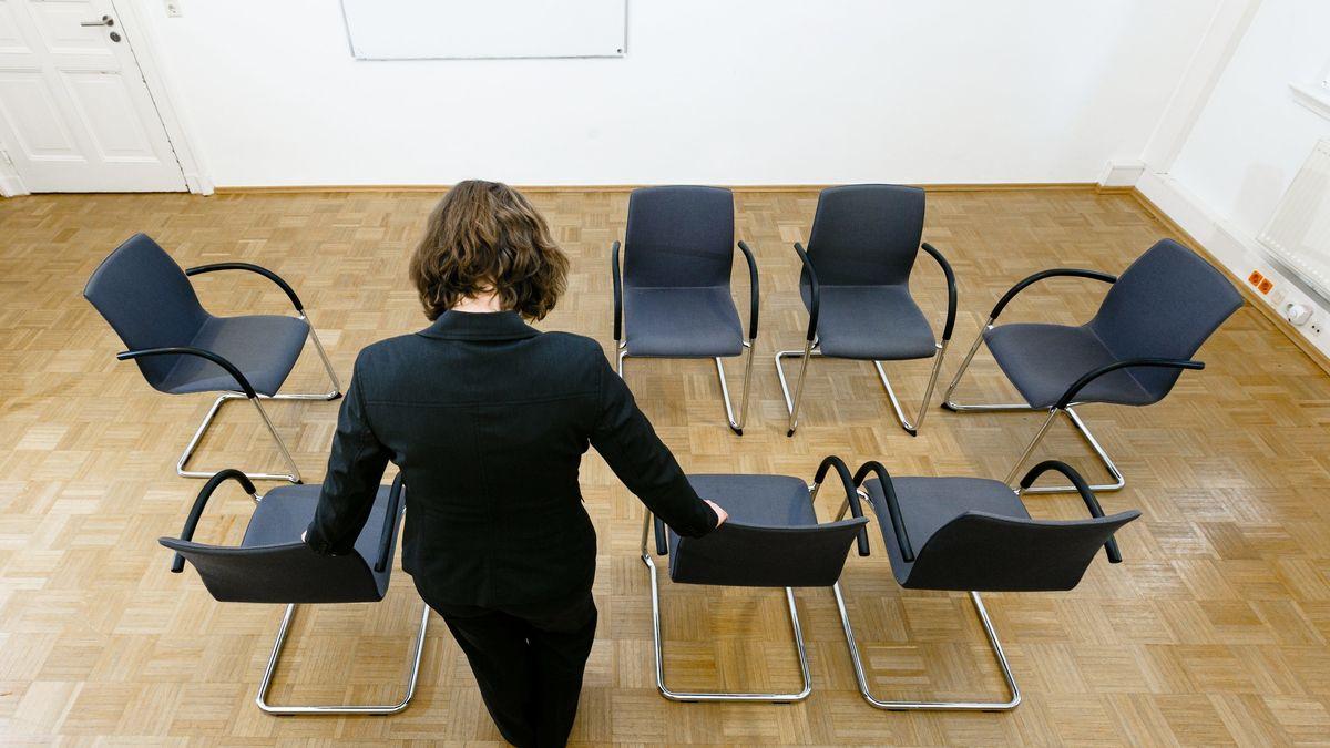 Eine Frau steht in einem Gruppenraum zwischen Stühlen.