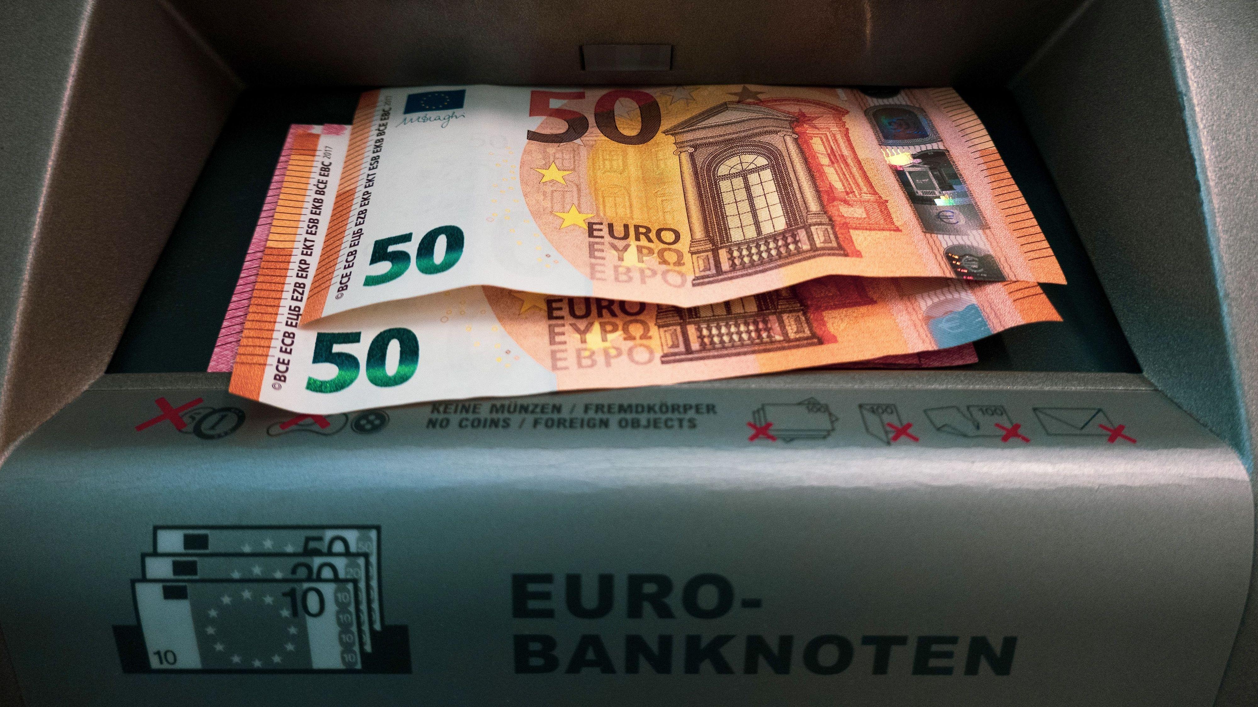 Zwei 50-Euro-Geldscheine und ein Zehn-Euro-Schein liegen im Ausgabefach eines Geldautomaten in Berlin
