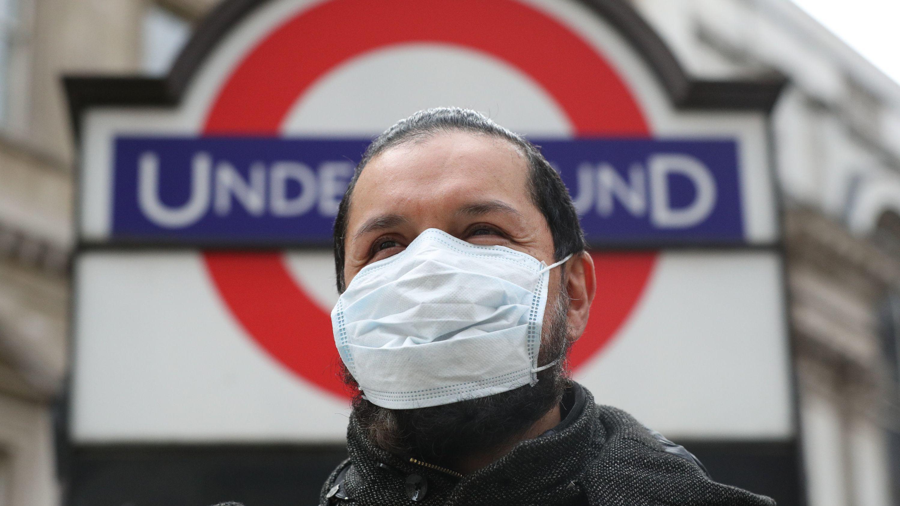 Ein Mann mit Mundschutz vor einem Eingang zur Londoner U-Bahn