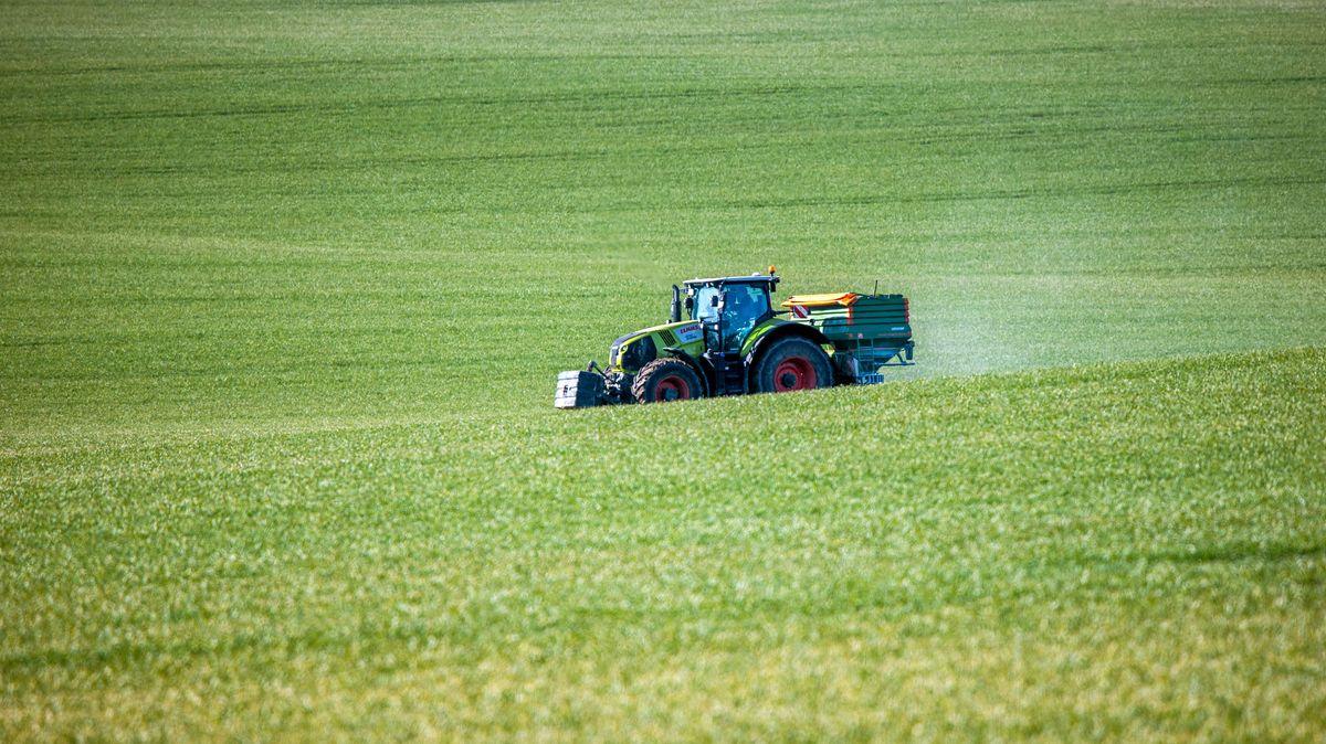 Ein Traktor mit einem Streuaufsatz verteilt Dünger auf einem Feld.