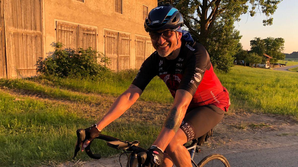Der 57-Jährige Thomas Metzger fährt lachend auf seinem Rennrad den Berg hinauf.