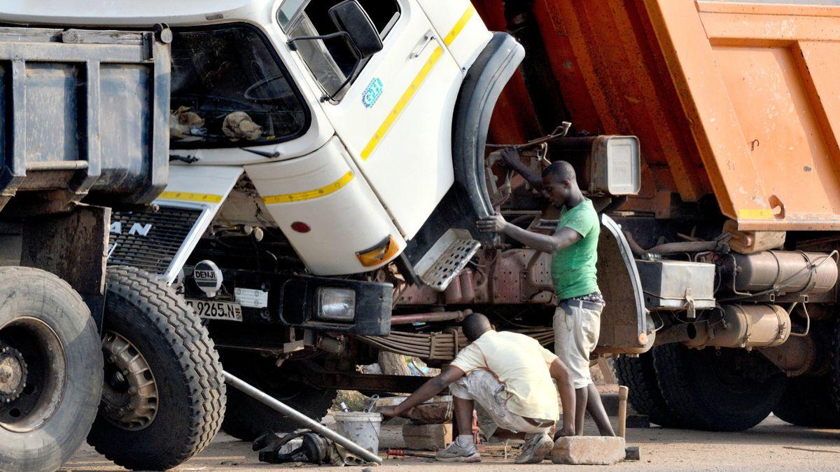 Zwei Männer reparieren einen LKW