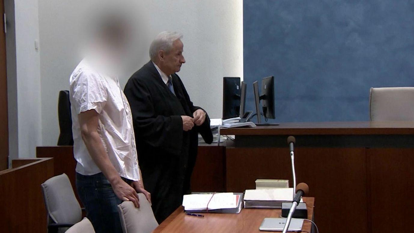 Der angeklagte mutmaßliche Brandstifter in blauer Jeans und weißem Hemd steht neben seinem Verteidiger vor der Anklagebank im Landgericht Hof.