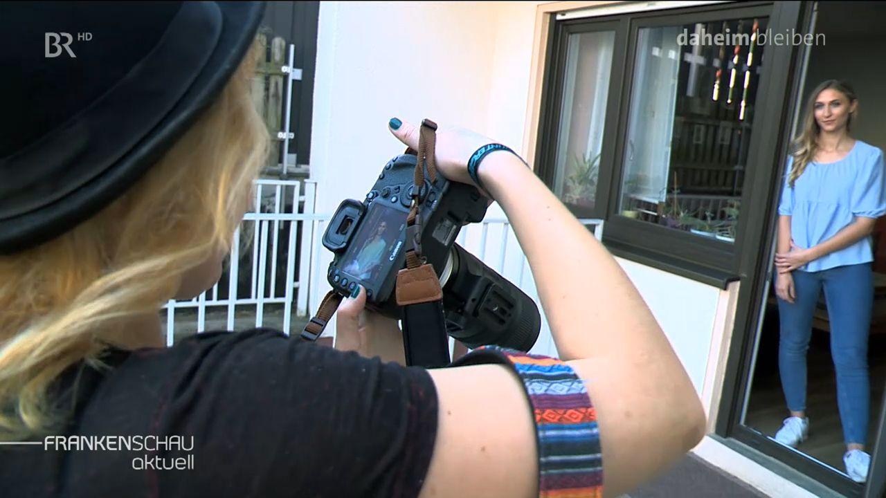 Eine Fotografin schaut auf den Bildschirm ihrer Kamera, im Türrahmen steht das Model