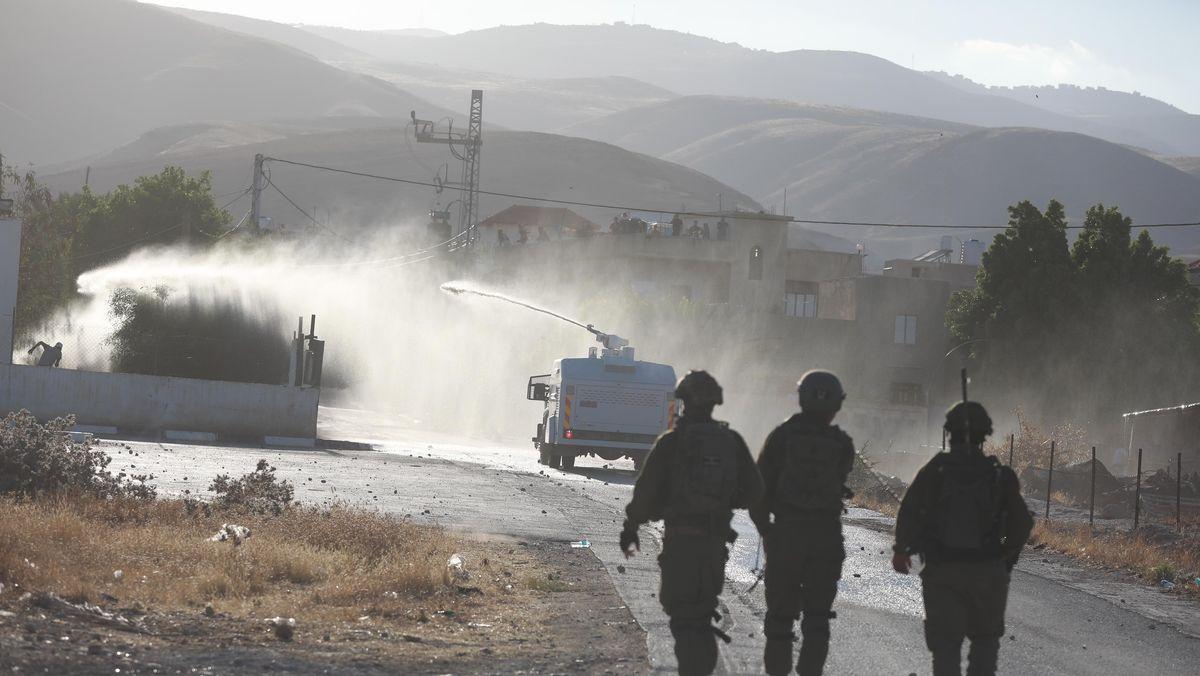 Drei Israelische Soldaten zu Fuß gehen im Westjordanland hinter einem Wasserwerfer hinterher.