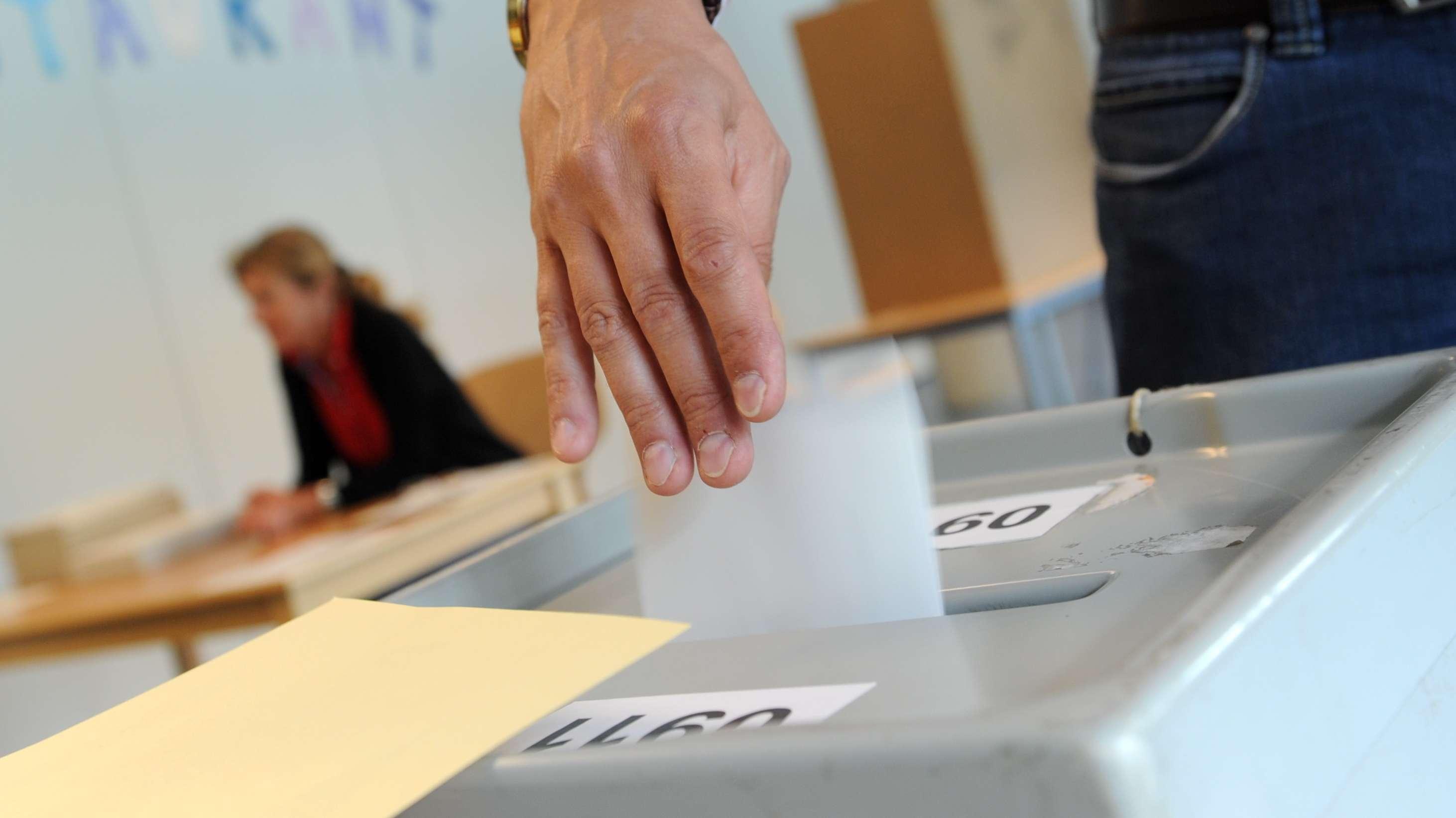 Ein Mann wirft in München einen Stimmzettel in eine Wahlurne