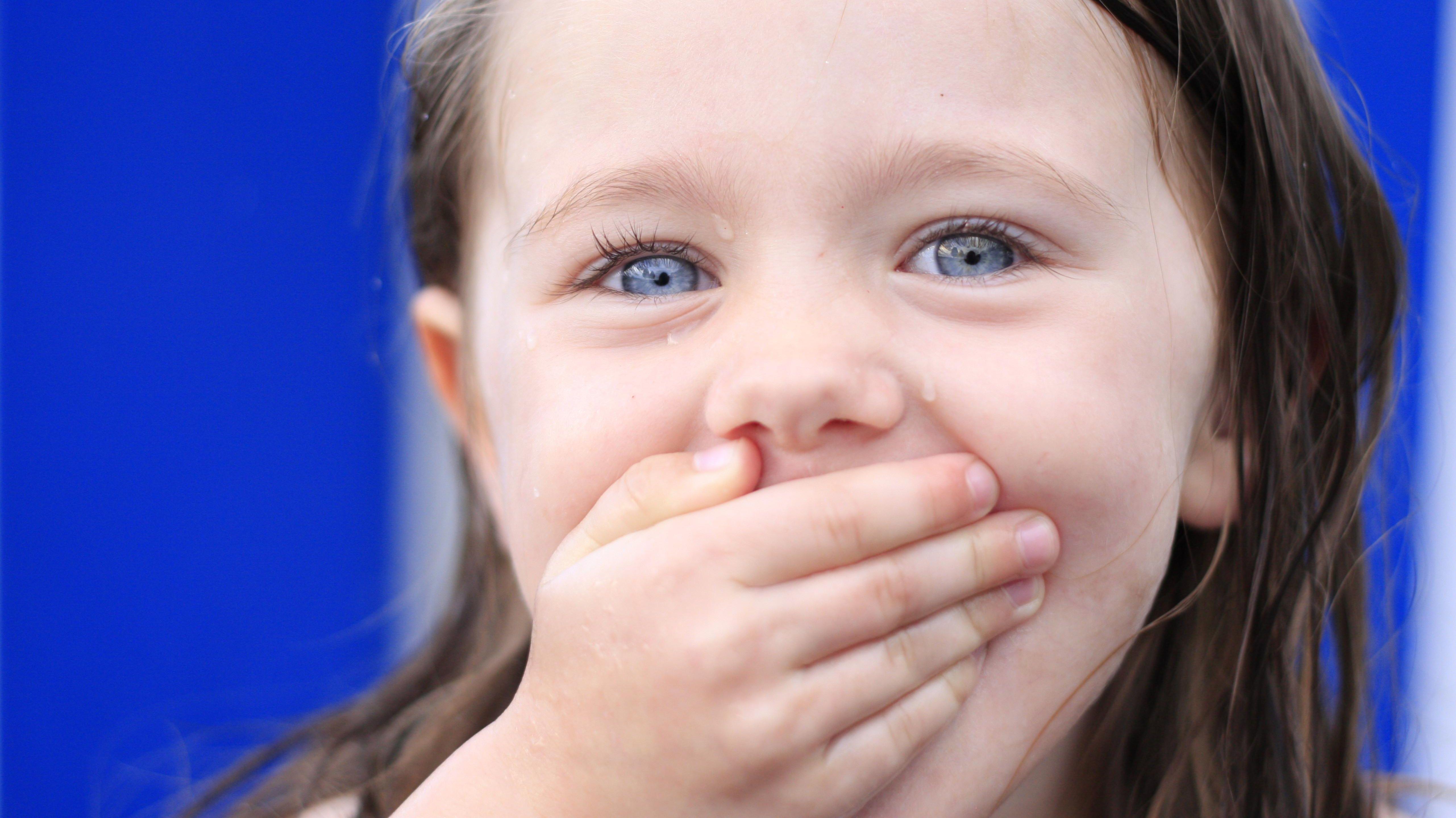 Mädchen hält sich den Mund zu