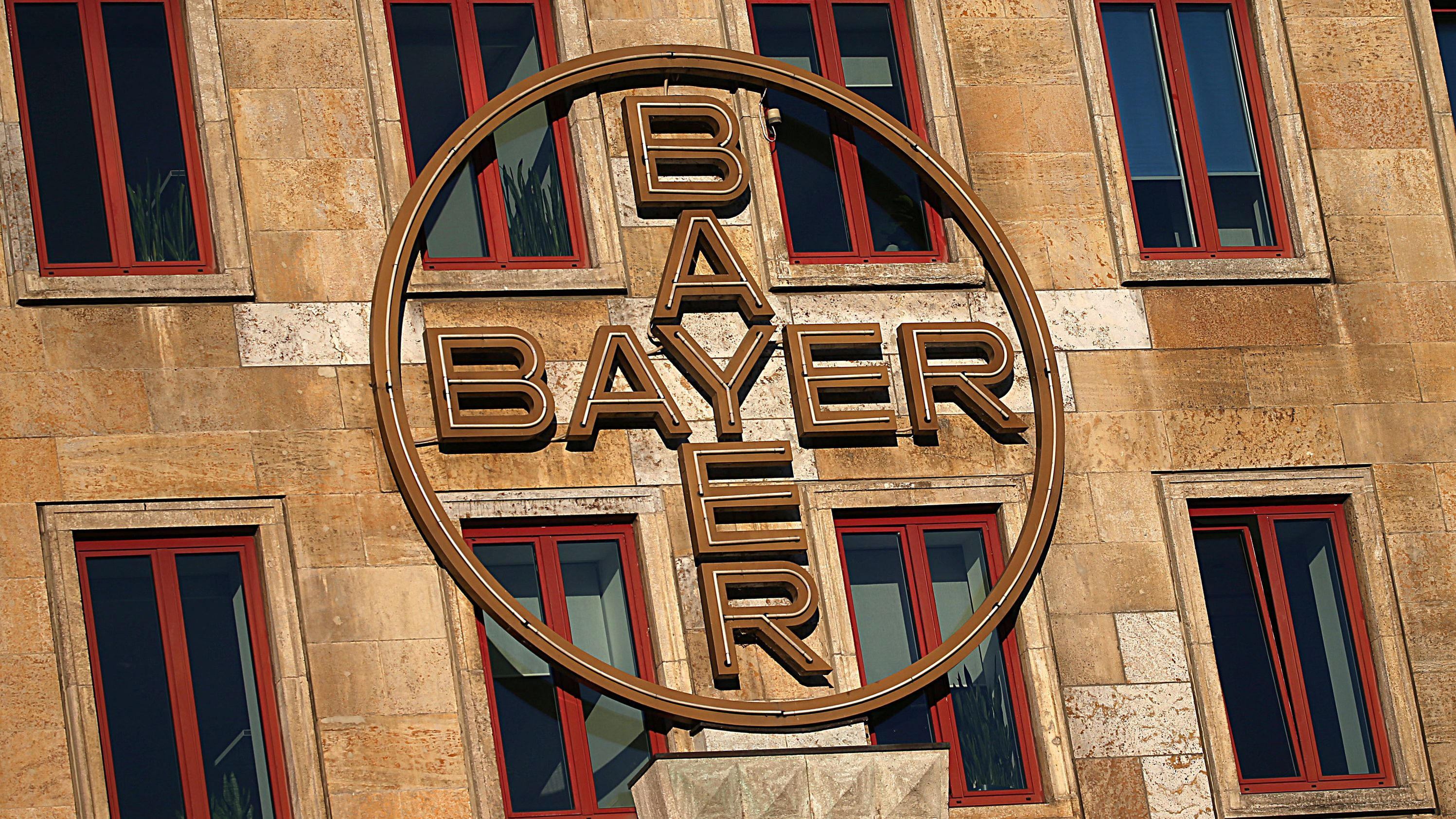 Das Bayer-Kreuz hängt an der Fassade eines Werksgebäudes von Bayer