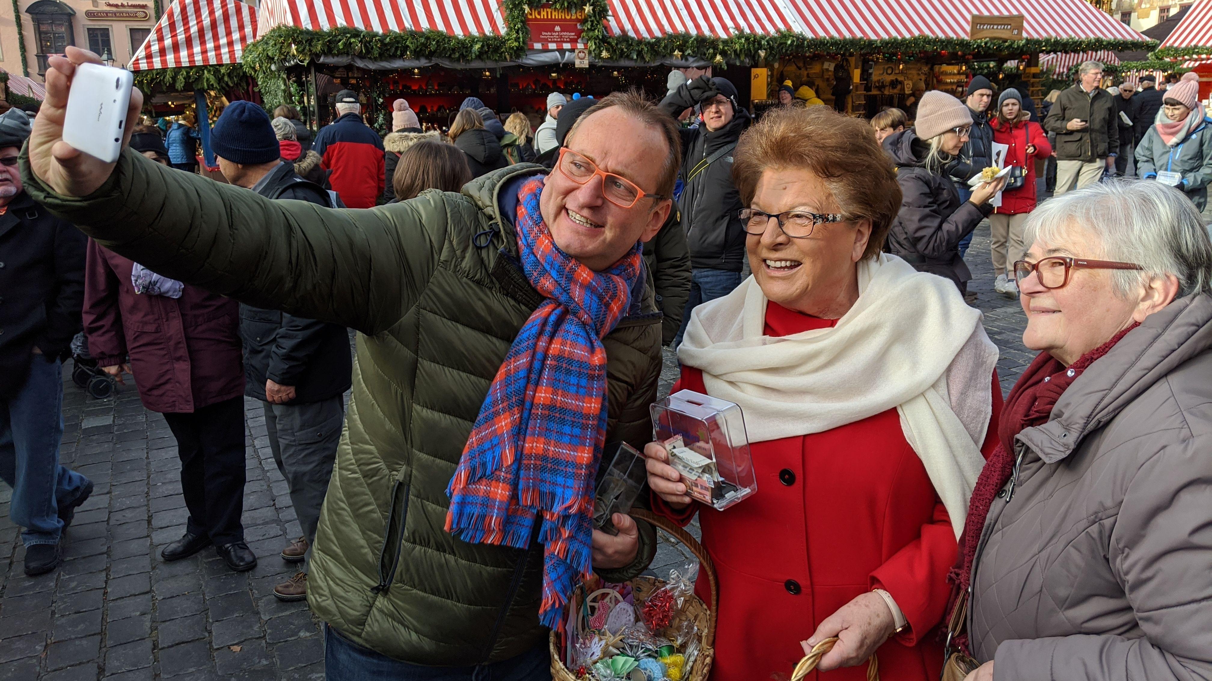 Volker Heißmann hält ein Handy und macht mit Barbara Stamm und einer Besucherin ein Selfie