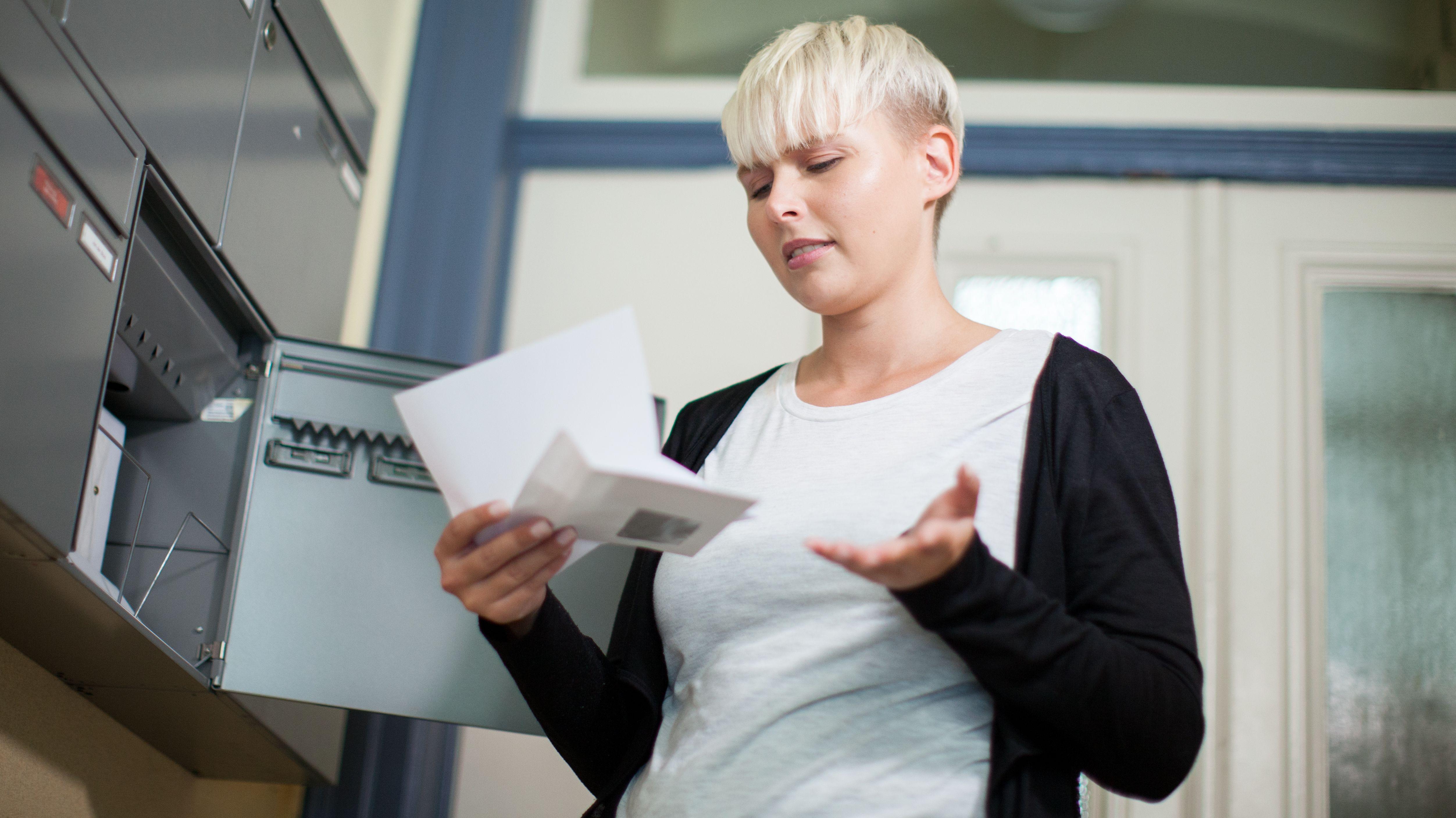 Eine junge Frau steht neben einem Briefkasten und öffnet einen Brief.